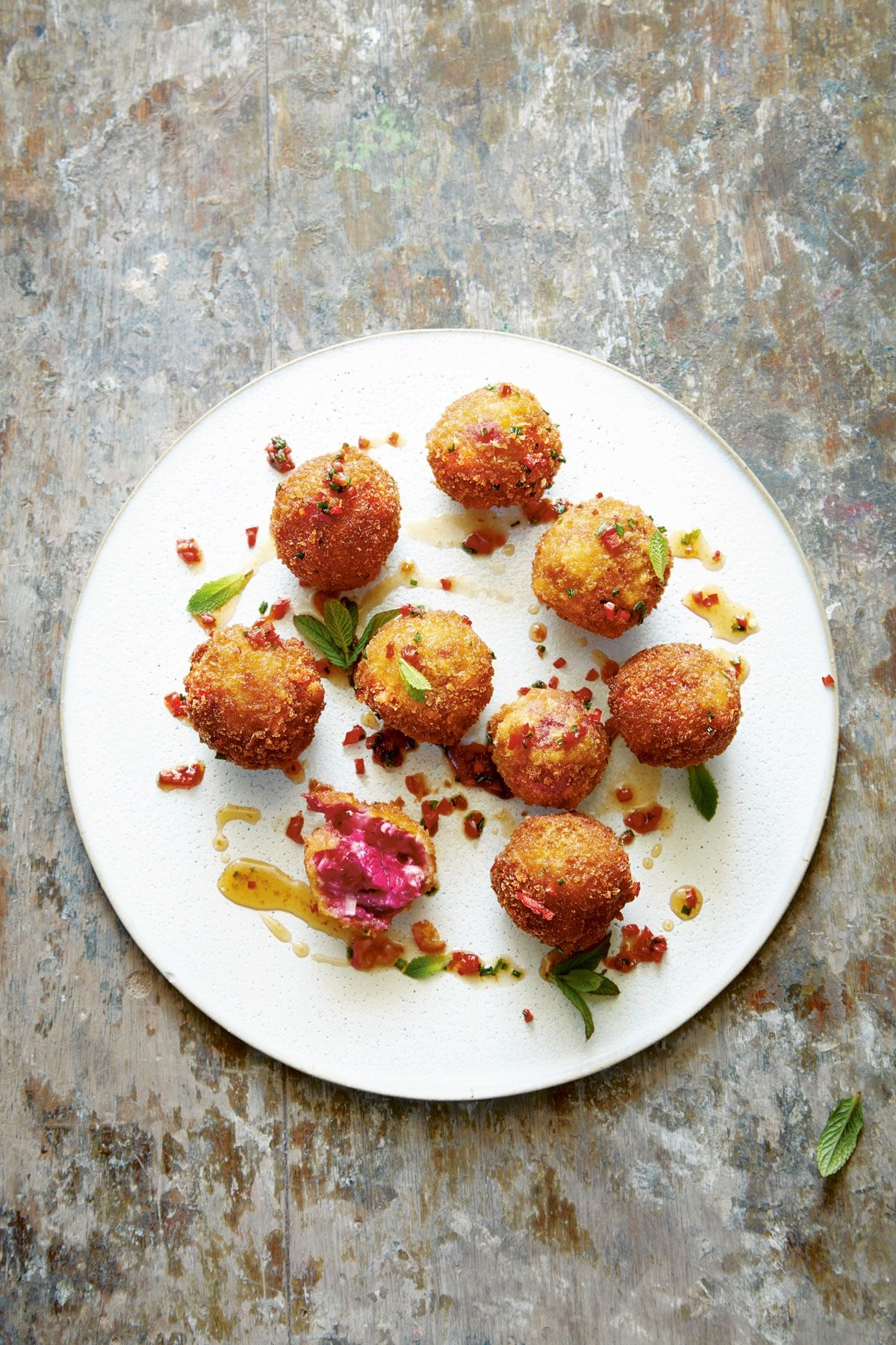 Goat's cheese croquettes on a large white plate. They have been dressed with maple syrup, red chilli, chives and mint.