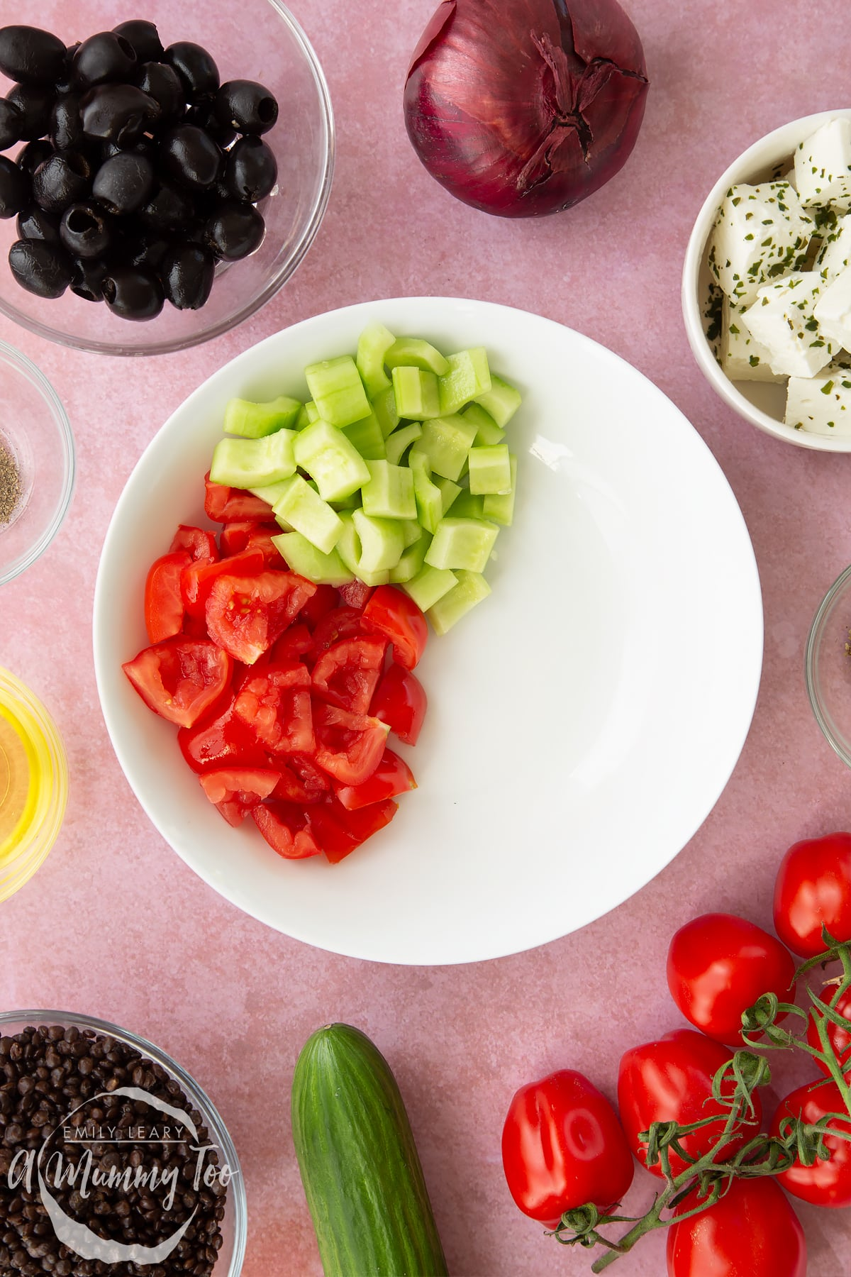 A white bowl containing chopped tomatoes and cucumber. Ingredients to make Greek lentil salad surround the bowl.