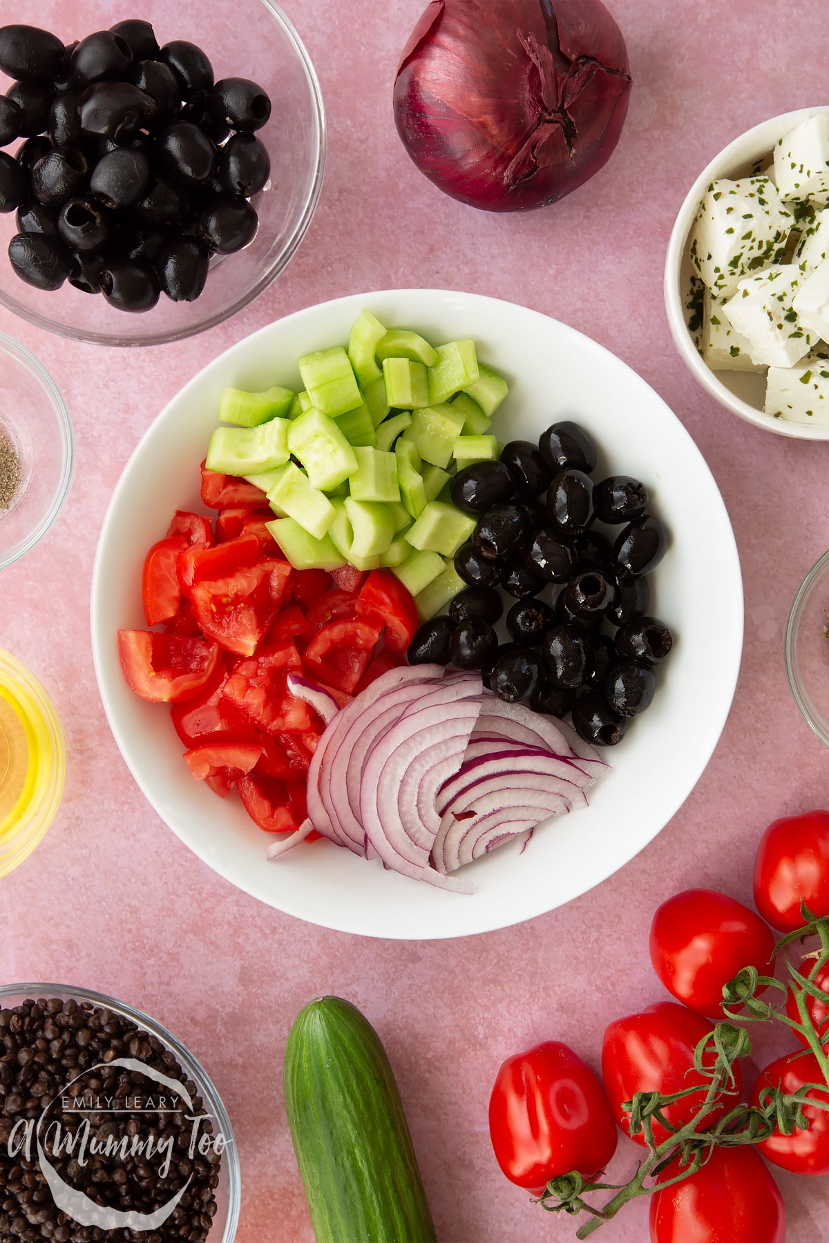 A white bowl containing chopped tomatoes, chopped cucumber, sliced red onion and whole black olives. Ingredients to make Greek lentil salad surround the bowl.