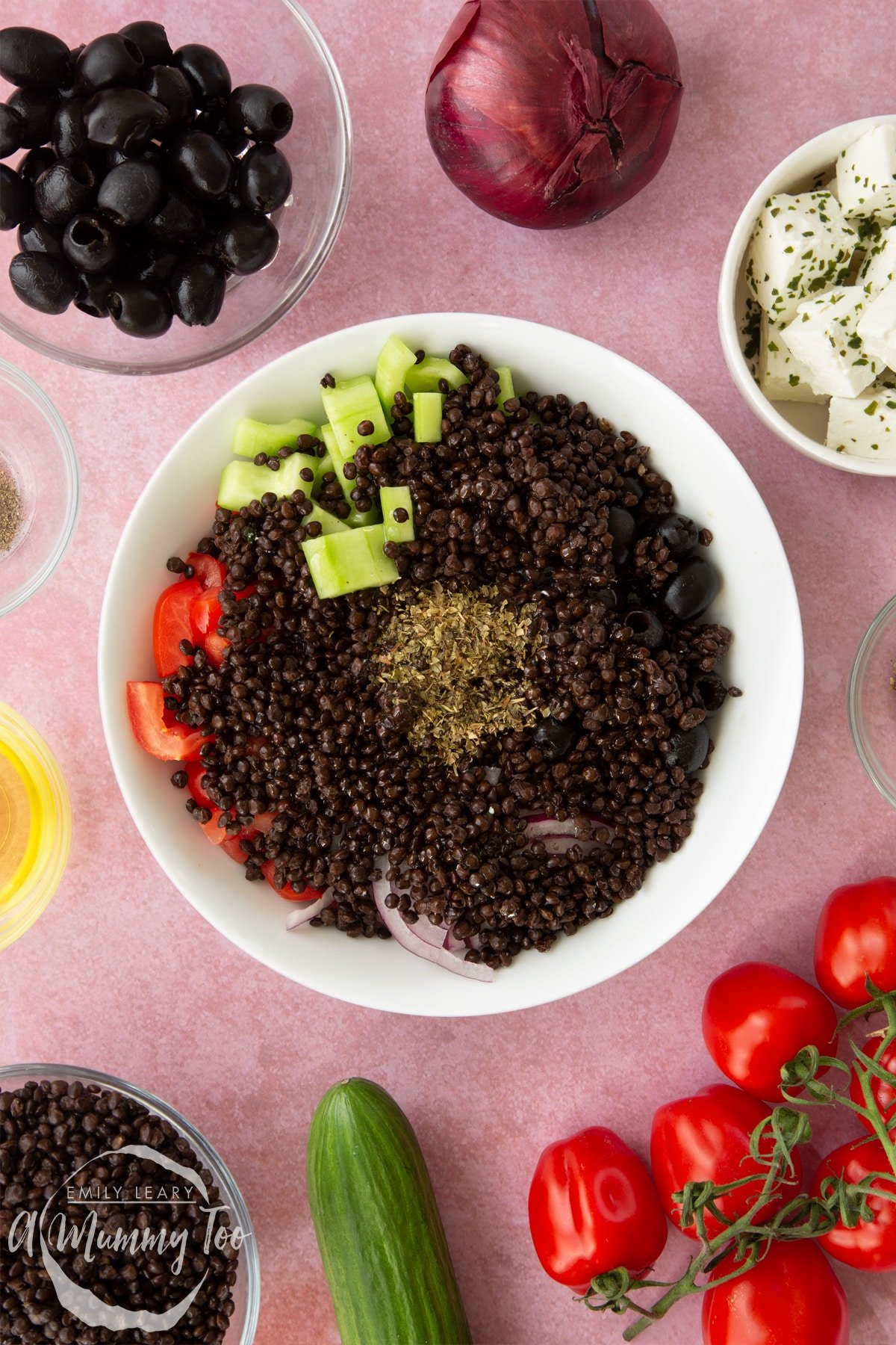 A white bowl containing chopped tomatoes, chopped cucumber, sliced red onion, whole black olives, cooked lentils, olive oil and oregano. Ingredients to make Greek lentil salad surround the bowl.