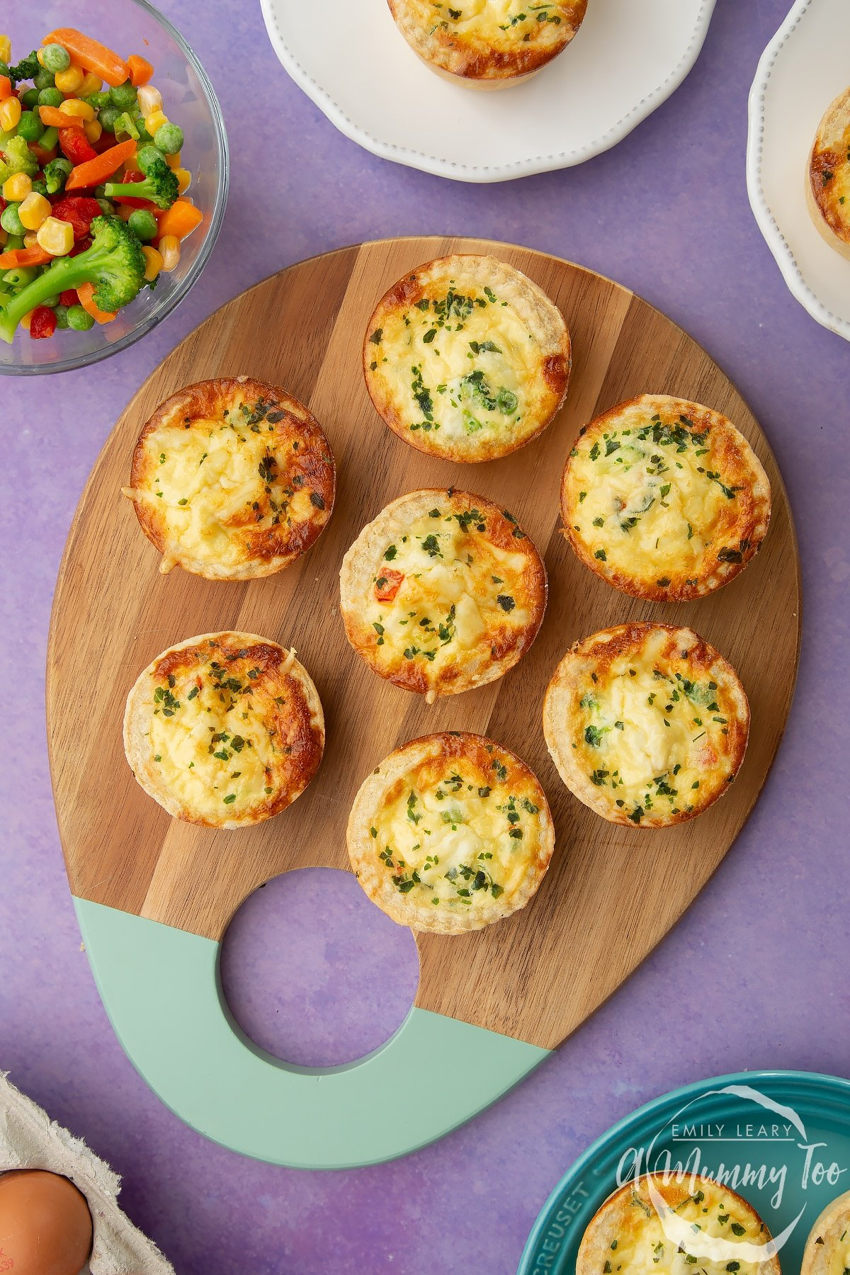 Mini vegetable quiches arranged on a wooden board.