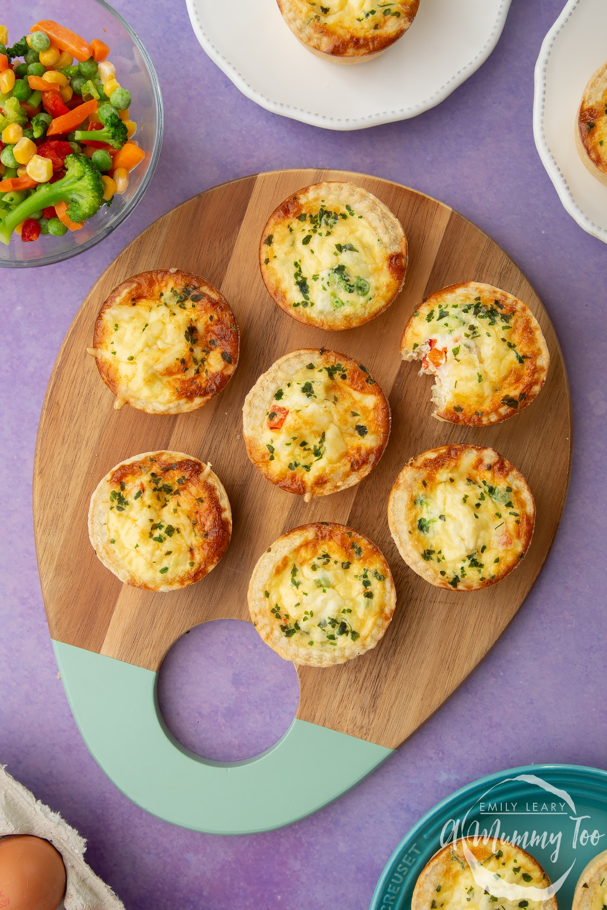 Mini vegetable quiches arranged on a wooden board. A bite has been taken out of one.