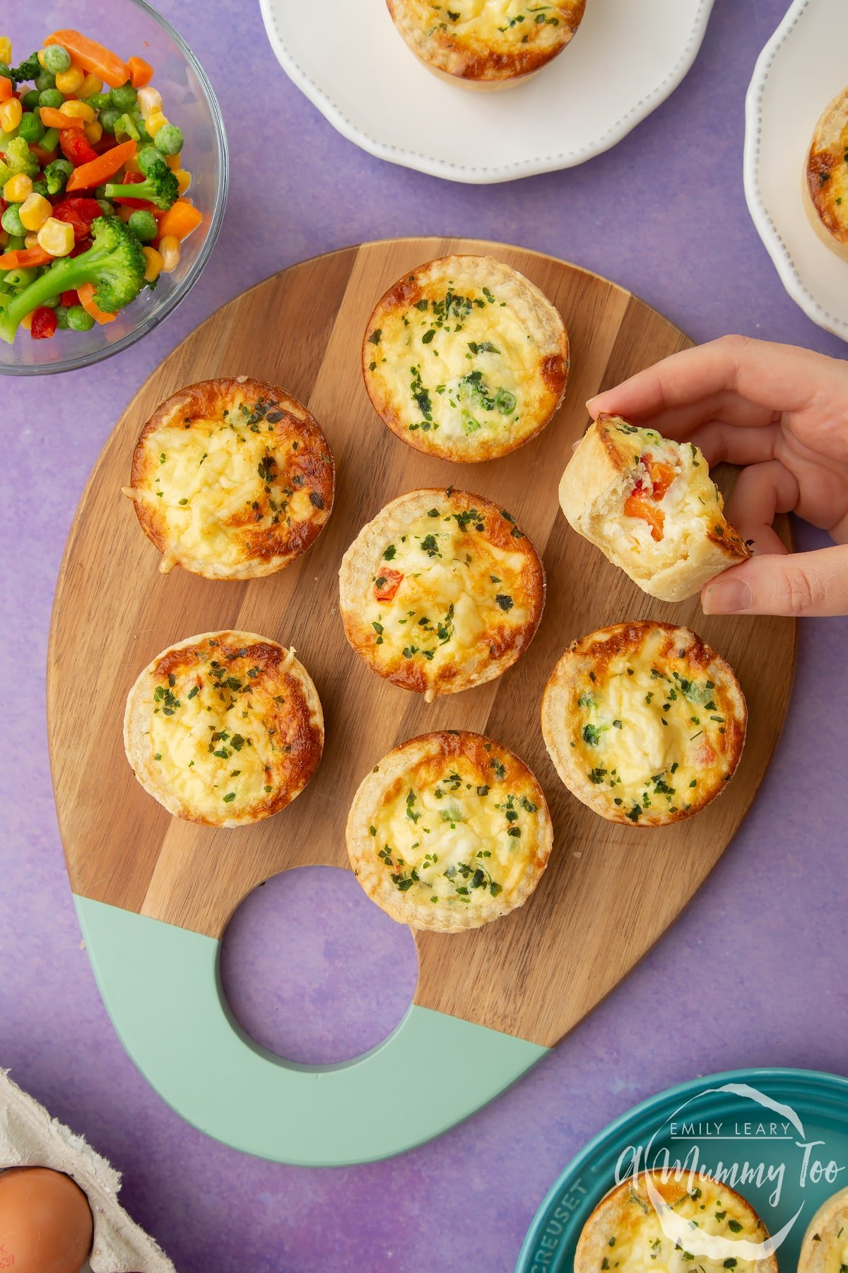 Mini vegetable quiches arranged on a wooden board. A hand holds ones with a bite taken out of it.