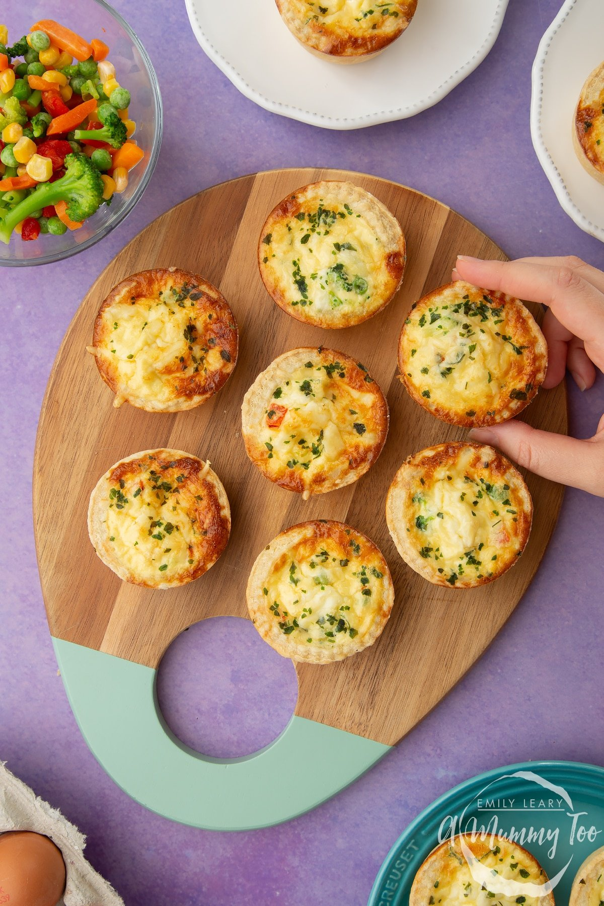 Mini vegetable quiches arranged on a wooden board. A hand reaches to take one.
