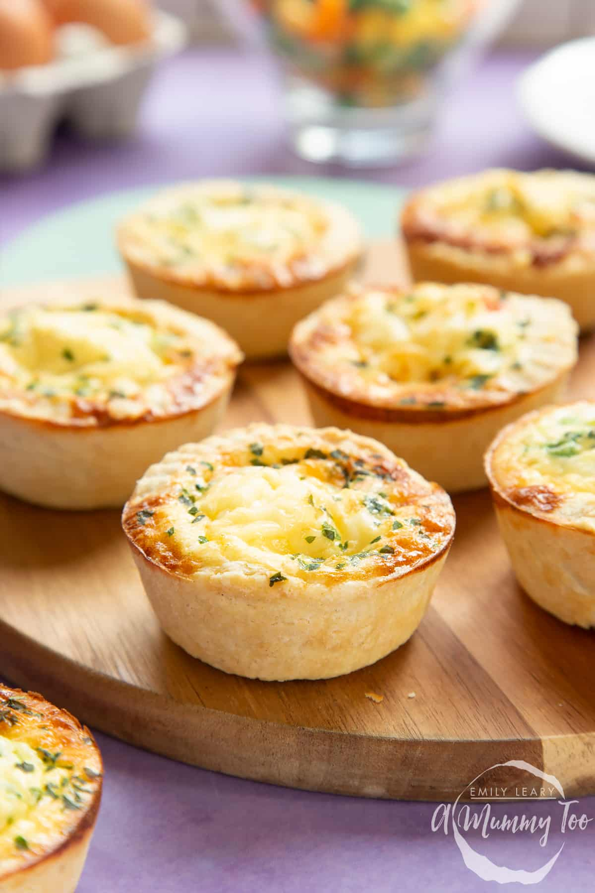 Mini vegetable quiches on a wooden board with ingredients in the background.