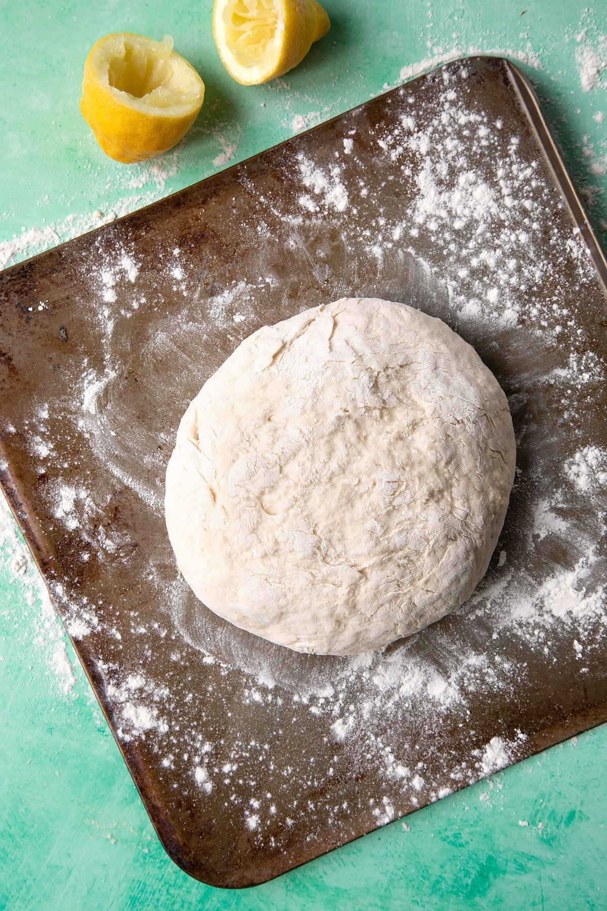 Dough to make a soda bread recipe without buttermilk placed on a floured baking sheet.