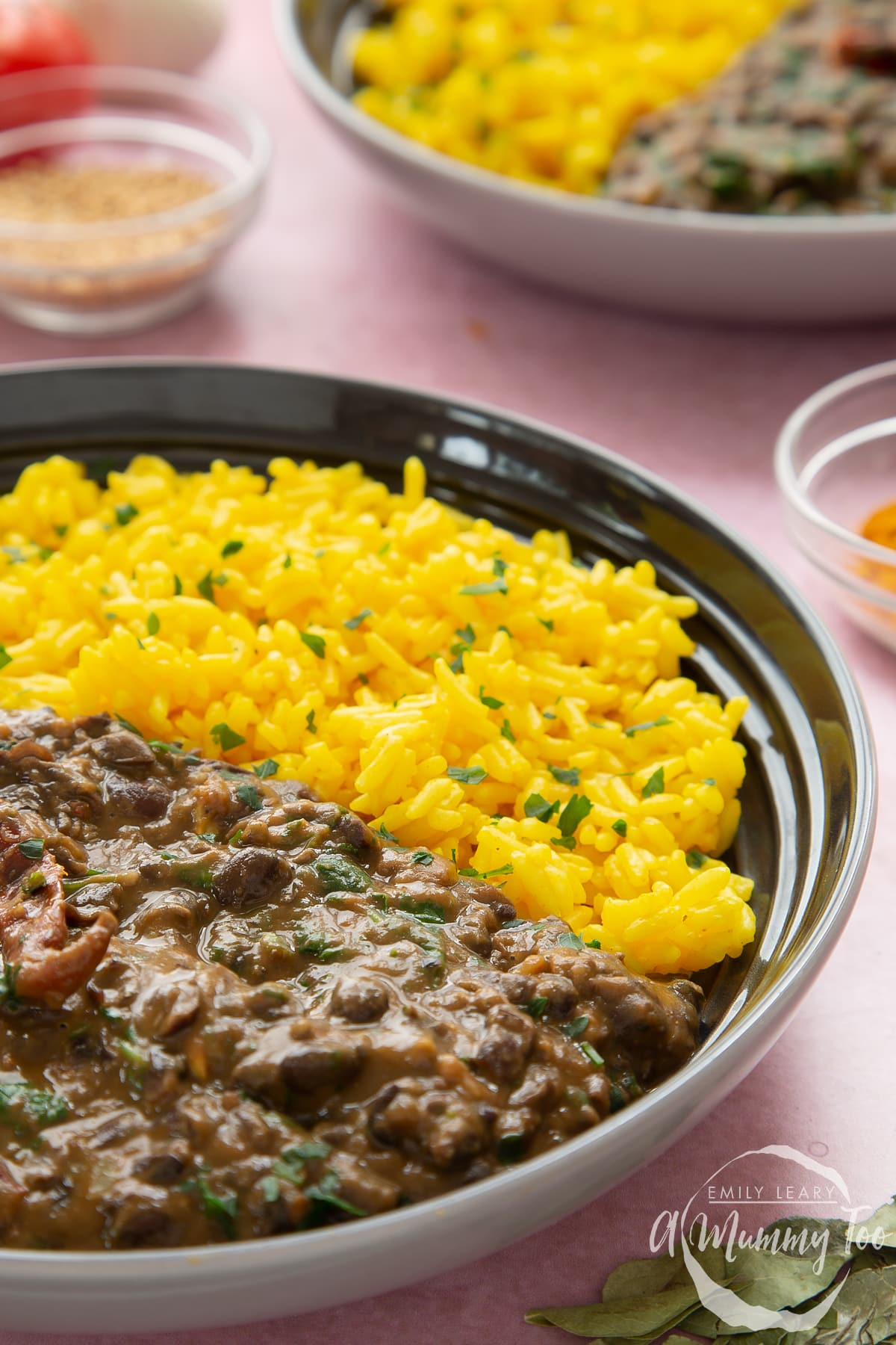 Black bean curry served to a shallow grey bowl with yellow rice scattered with chopped coriander.