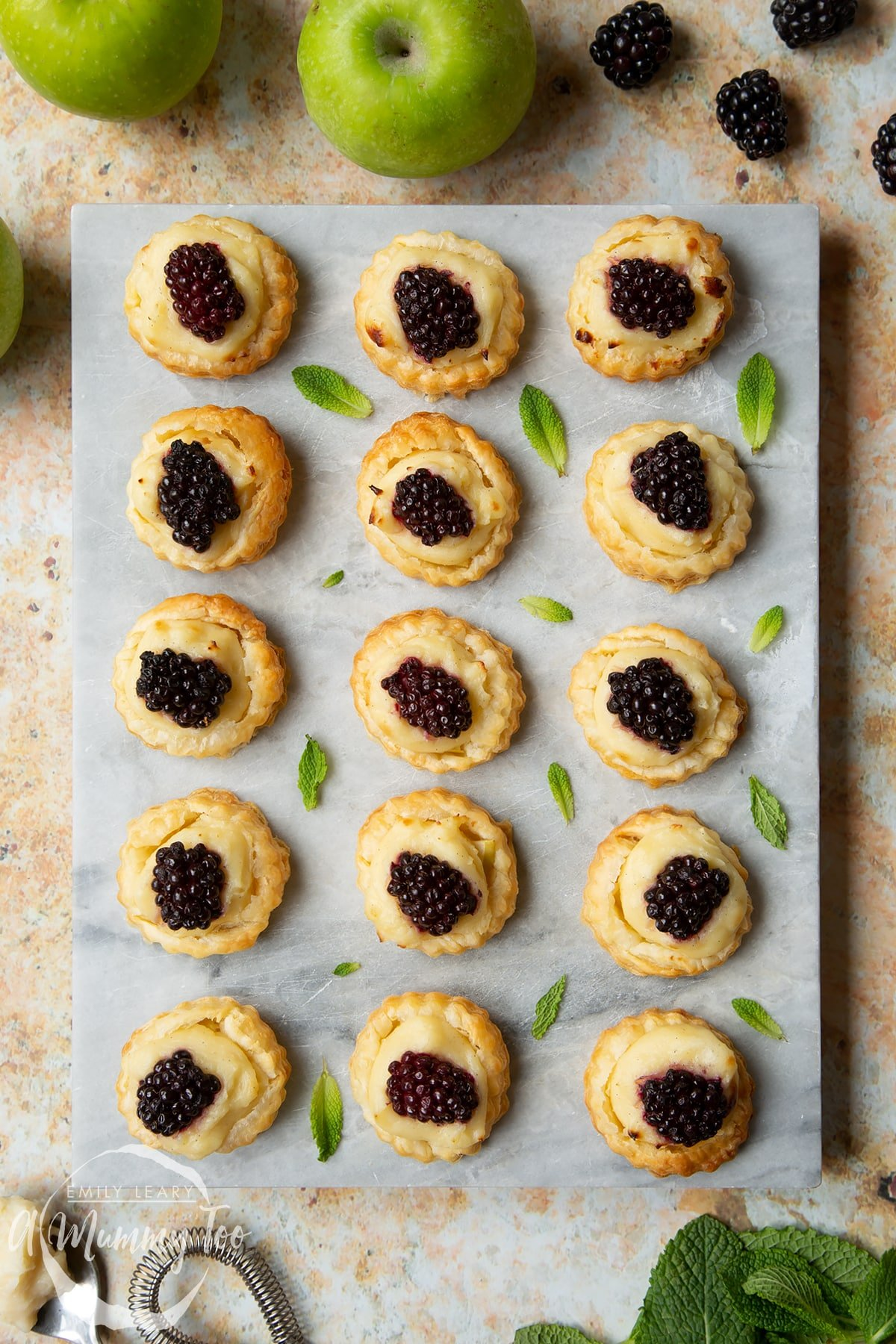 Sixteen blackberry tartlets comprised of a small puff pastry disc topped with sliced apple, pastry cream and a blackberry sit on a marble board with tiny mint leaves scattered around them.