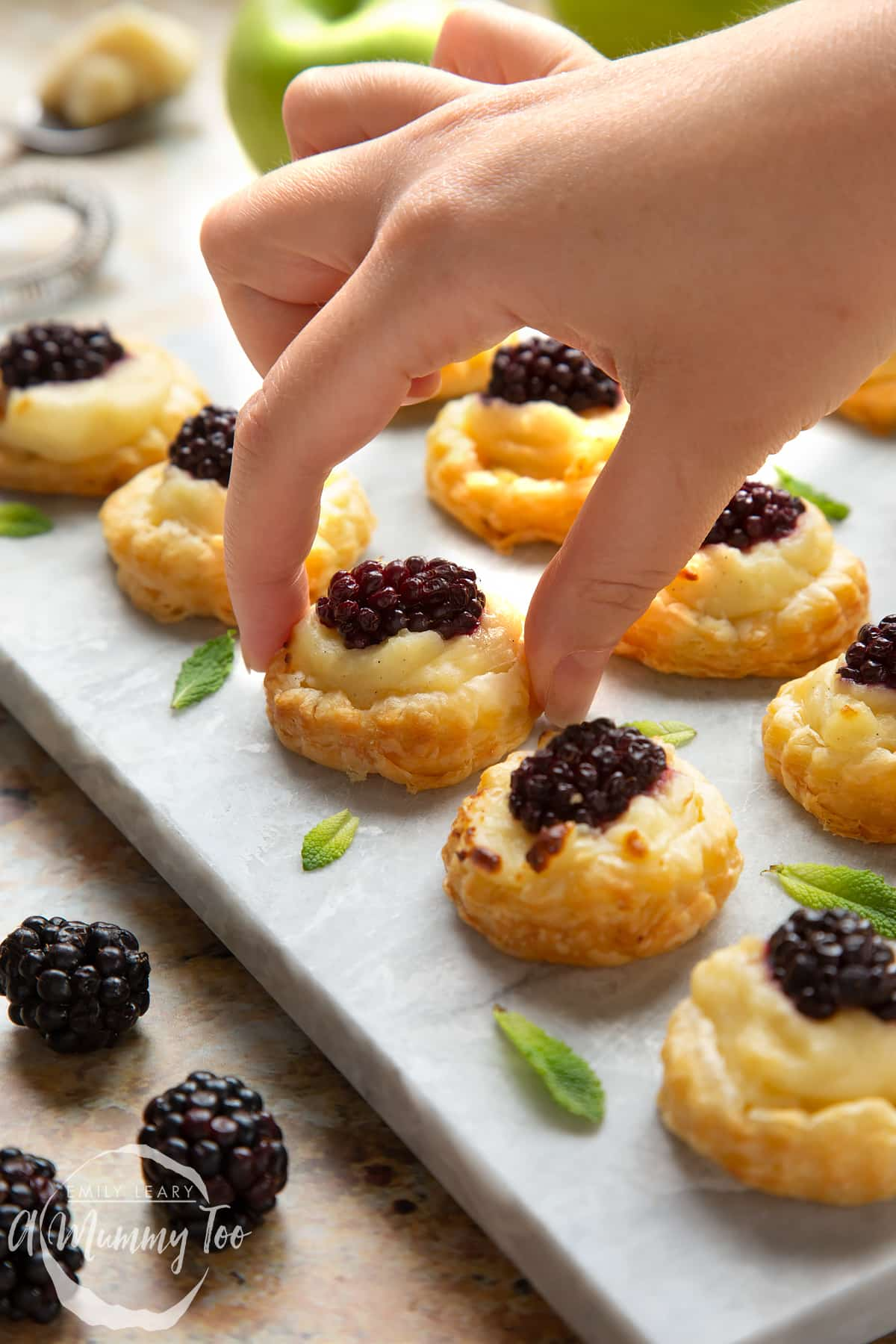 A hand reaches in to take a blackberry tartlet, comprised of a small puff pastry disc topped with sliced apple, pastry cream and a blackberry. More blackberry tartlets sit on the marble board around it.