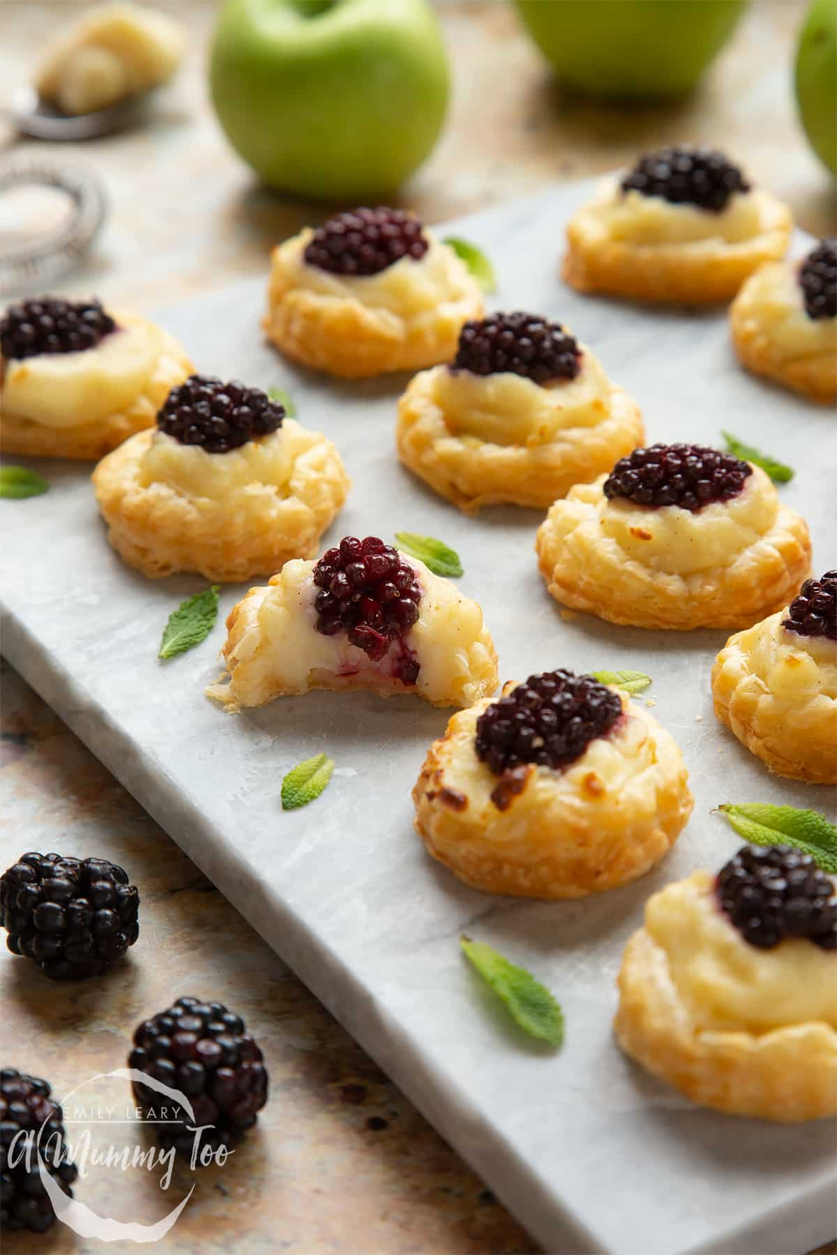 Sixteen blackberry tartlets comprised of a small puff pastry disc topped with sliced apple, pastry cream and a blackberry sit on a marble board with tiny mint leaves scattered around them. One has a bite taken out of it.