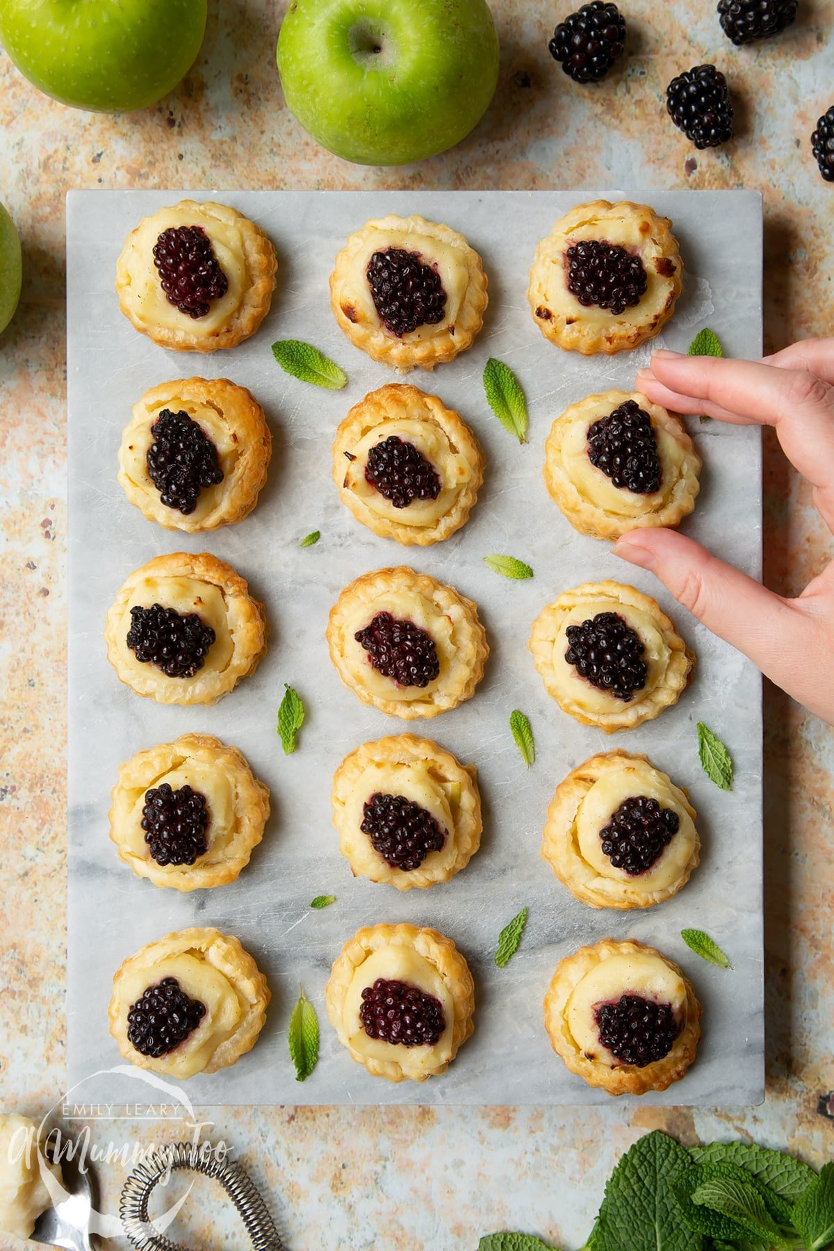 Blackberry tartlets comprised of a small puff pastry disc topped with sliced apple, pastry cream and a blackberry sit on a marble board with tiny mint leaves scattered around them. A hand holds one of the tarts.
