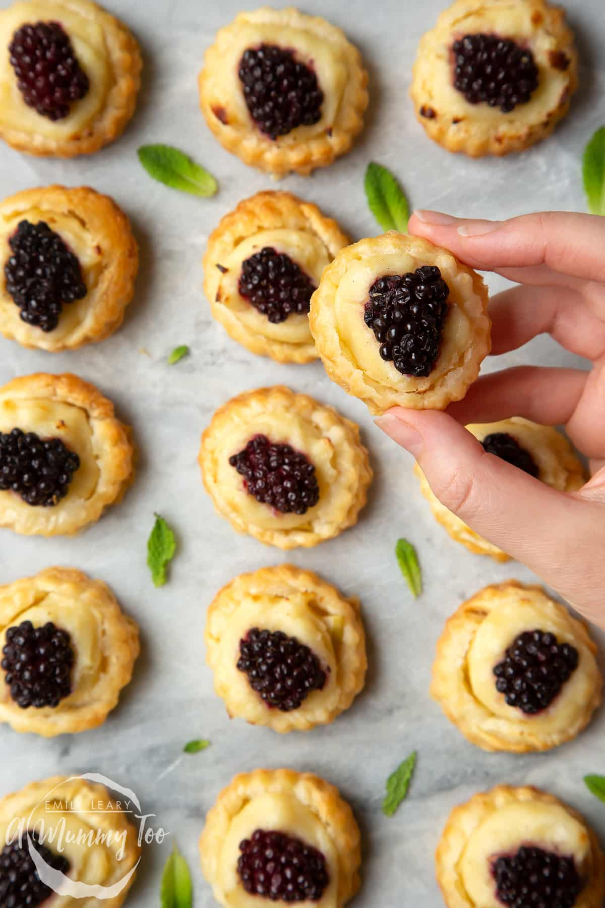 Sixteen blackberry tartlets comprised of a small puff pastry disc topped with sliced apple, pastry cream and a blackberry sit on a marble board with tiny mint leaves scattered around them. A hand holds one of the tarts.