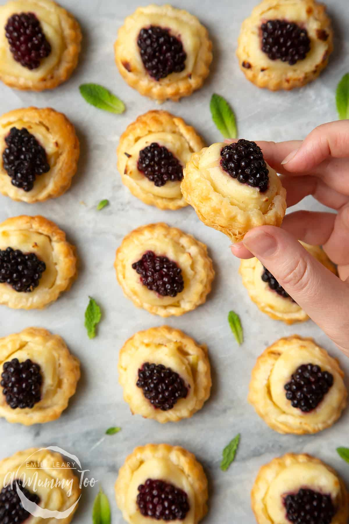 A hand holds a blackberry tartlet, comprised of a small puff pastry disc topped with sliced apple, pastry cream and a blackberry. More blackberry tartlets sit on the marble board in the background.