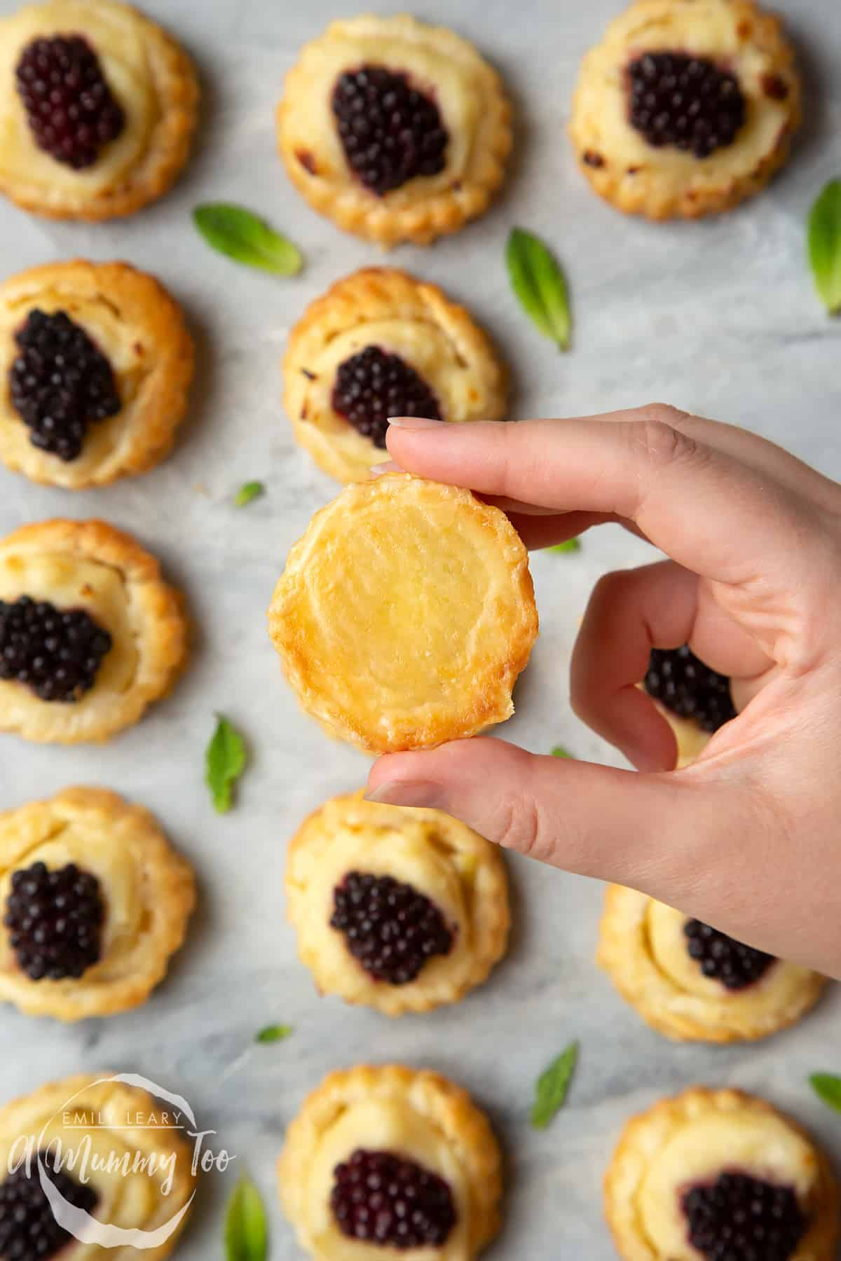 A hand holding a blackberry tartlet, showing the golden underside. More blackberry tartlets comprised of a small puff pastry disc topped with sliced apple, pastry cream and a blackberry sit on the marble board with tiny mint leaves scattered around them.
