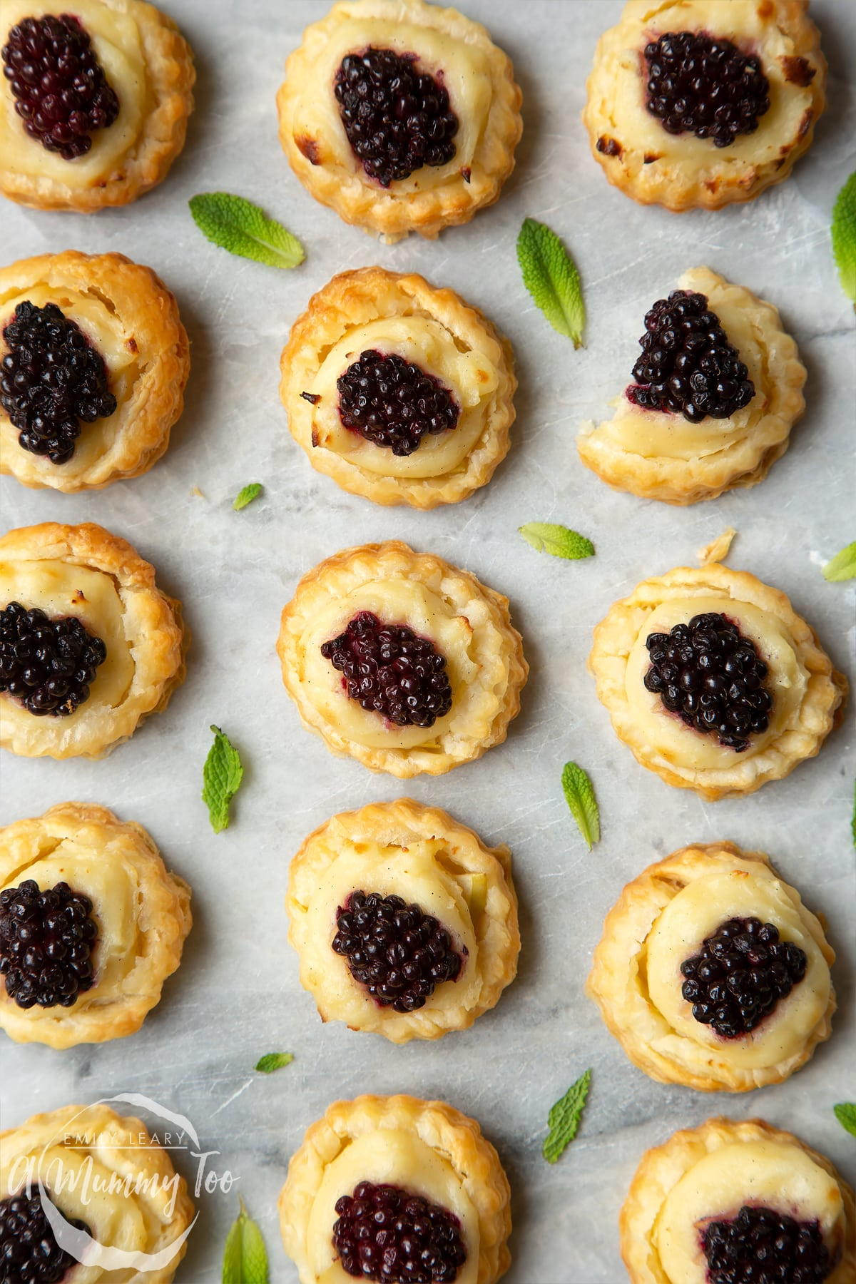 16 blackberry tartlets comprised of a small puff pastry disc topped with sliced apple, pastry cream and a blackberry sit on the marble board with tiny mint leaves scattered around them.