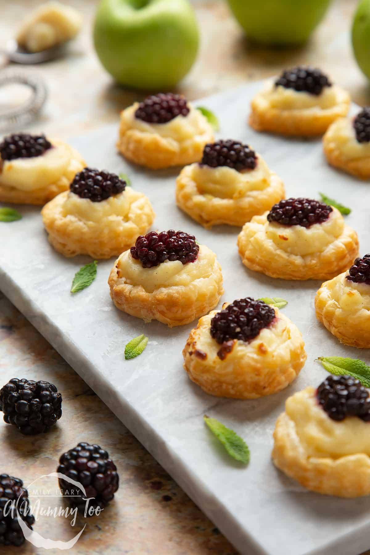 Blackberry tartlets comprised of a small puff pastry disc topped with sliced apple, pastry cream and a blackberry sit on a marble board with tiny mint leaves scattered around them.