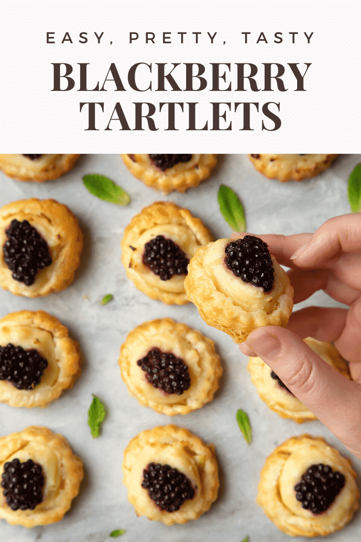 Blackberry tartlets on a marble board with tiny mint leaves scattered around them. A hand holds one of the tarts. Caption reads: easy, pretty, tasty blackberry tartlets.