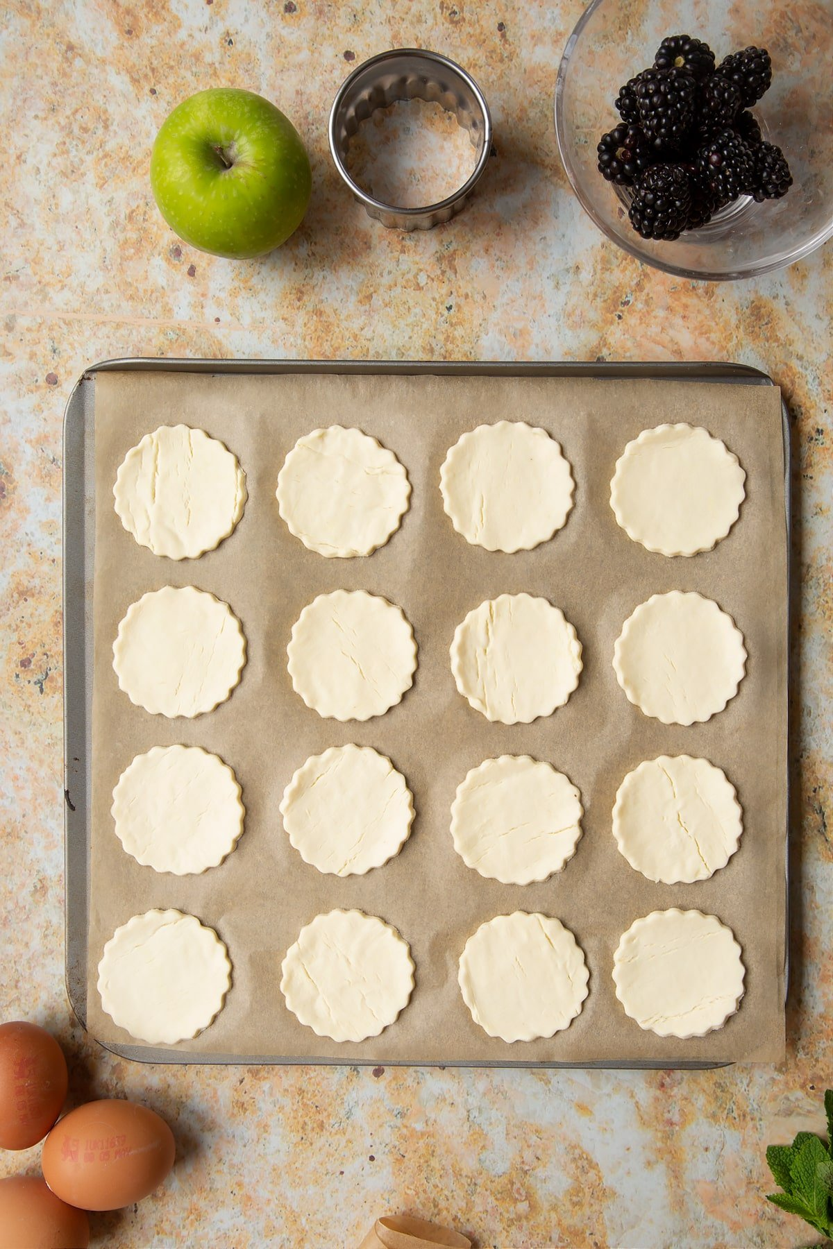 16 raw puff pastry discs sit on a lined baking sheet, ready to be baked.