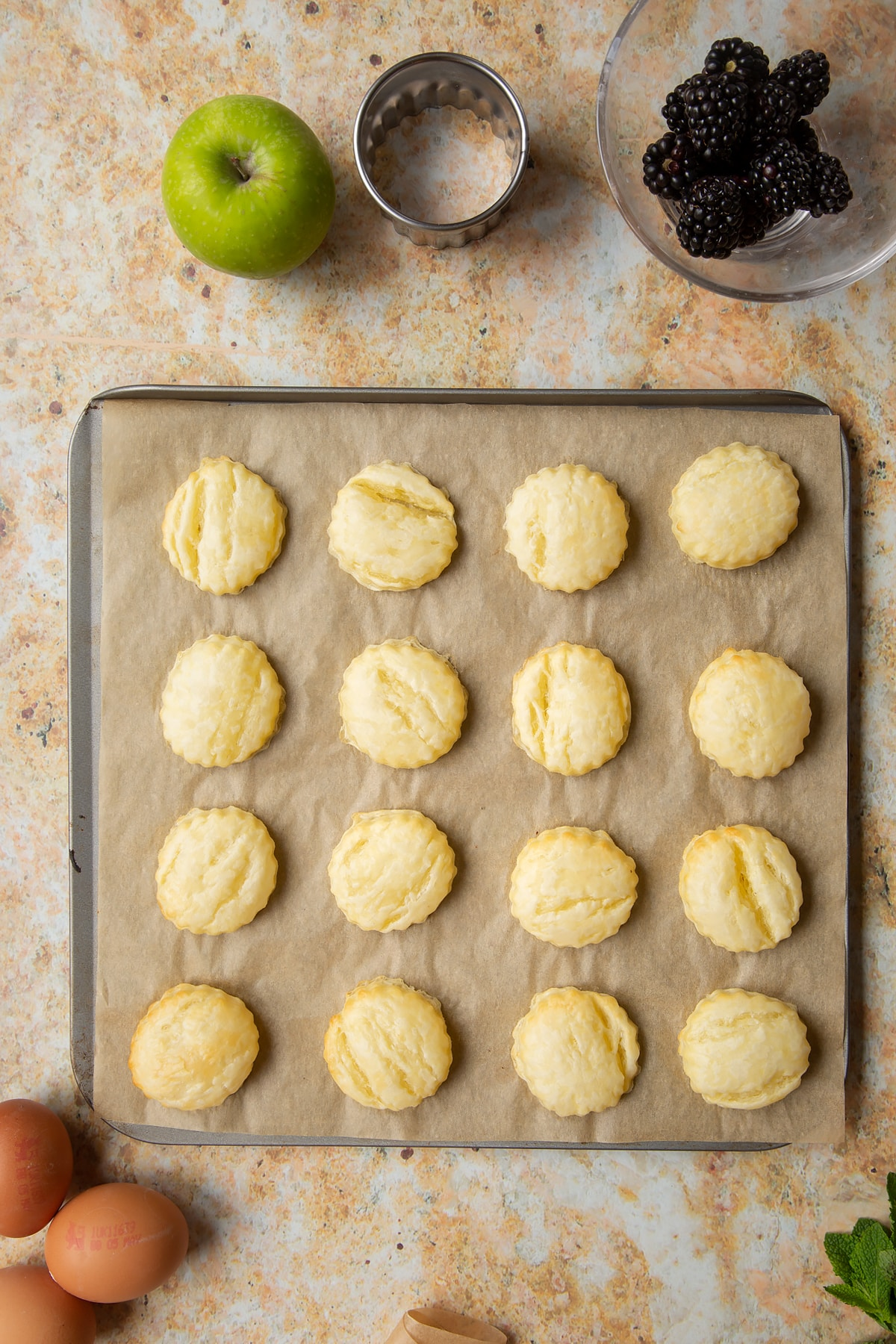 16 part-baked puff pastry discs sit on a lined baking sheet.