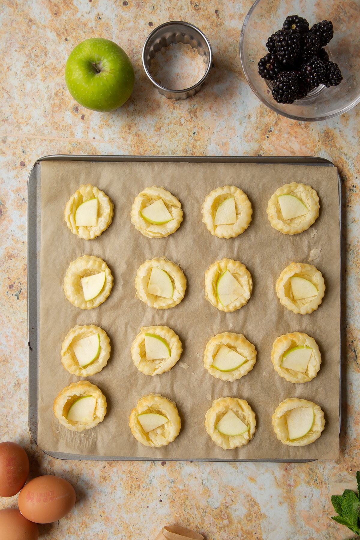 16 puff pastry discs topped with sliced apple sit on a lined baking sheet.