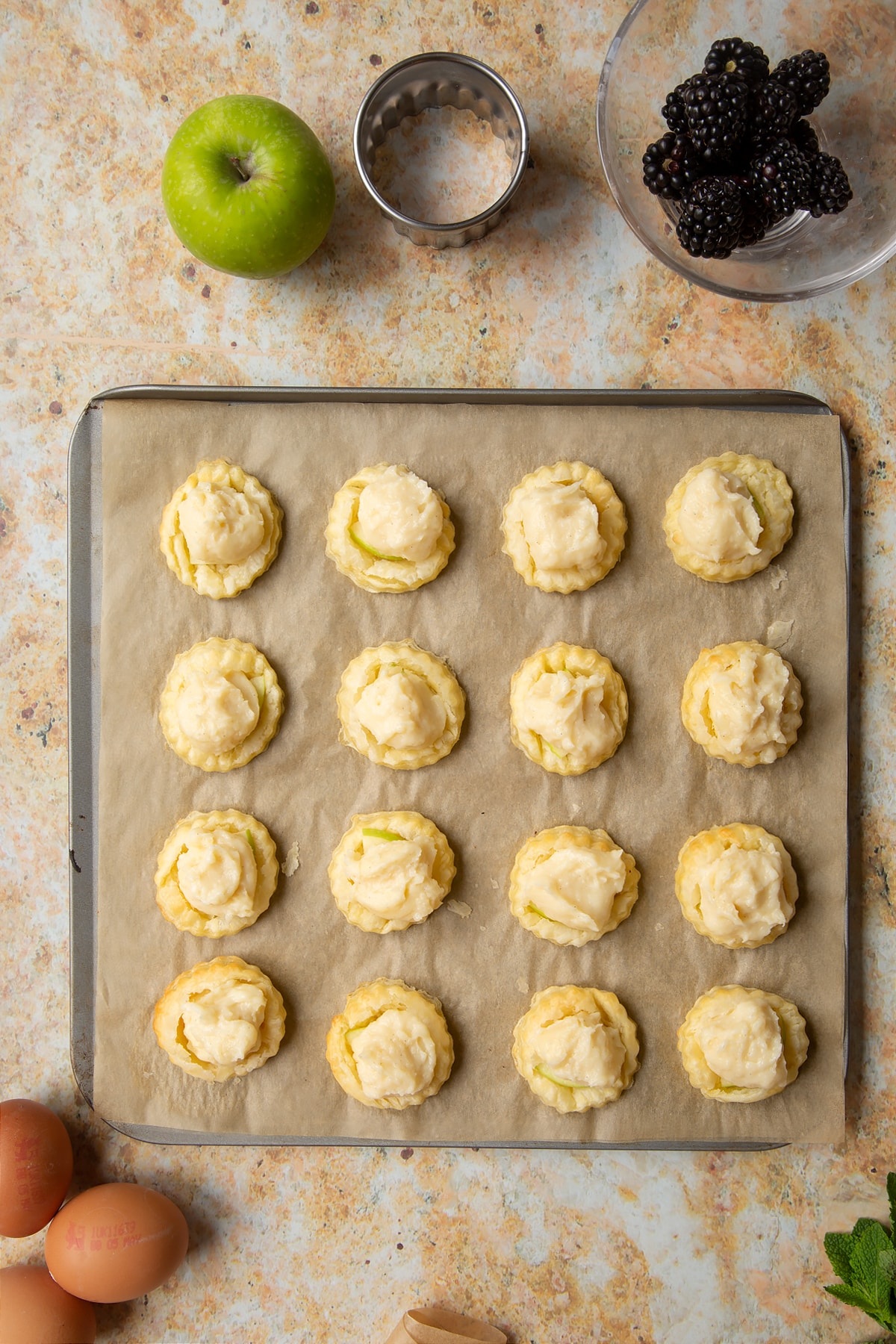 16 puff pastry discs topped with sliced apple and pastry cream sit on a lined baking sheet.