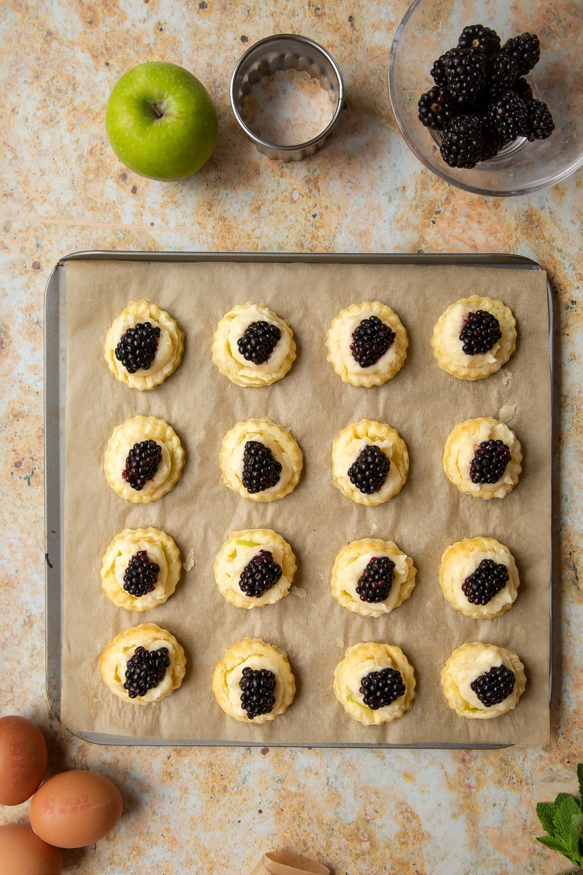 16 blackberry tartlets comprised of a small puff pastry disc topped with sliced apple, pastry cream and a blackberry sit on a lined baking sheet, ready to be baked.