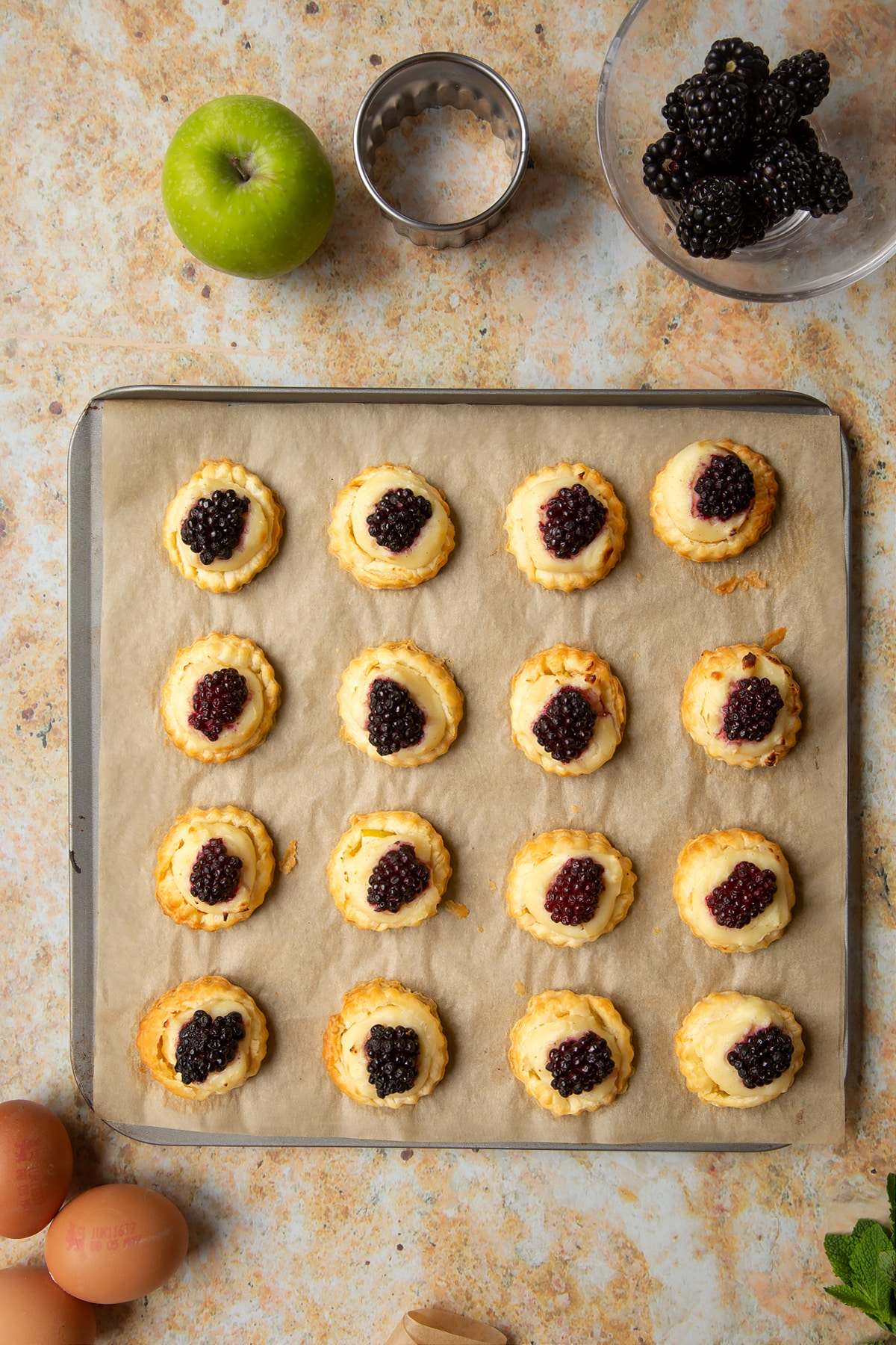16 freshly baked blackberry tartlets comprised of a small puff pastry disc topped with sliced apple, pastry cream and a blackberry sit on a lined baking sheet.