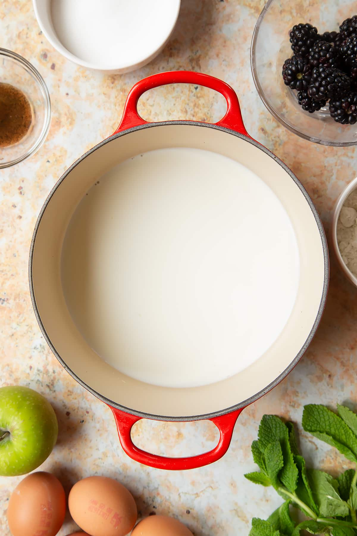 A saucepan filled with milk, surrounded by ingredients to make blackberry tartlets.