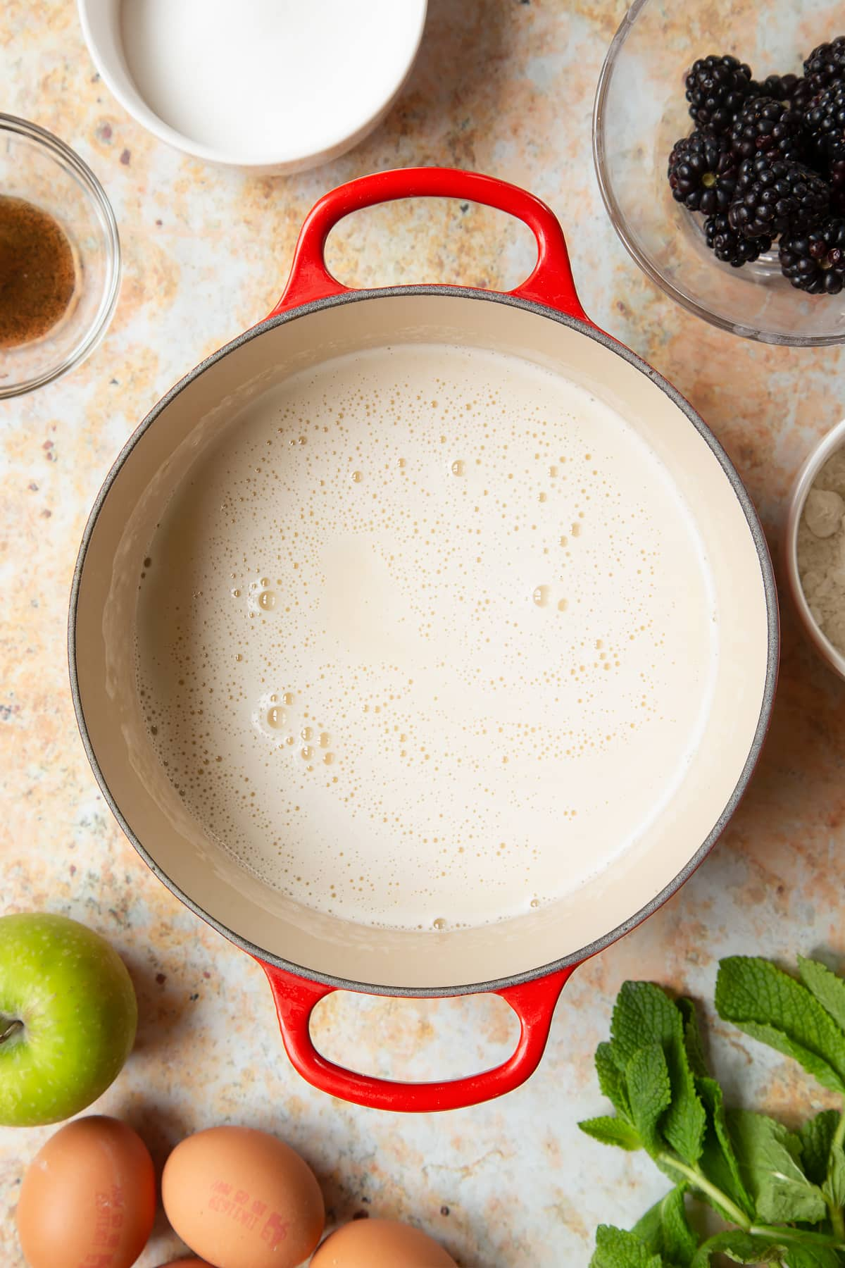 A saucepan filled with milk, eggs, flour, sugar and vanilla, surrounded by ingredients to make blackberry tartlets.