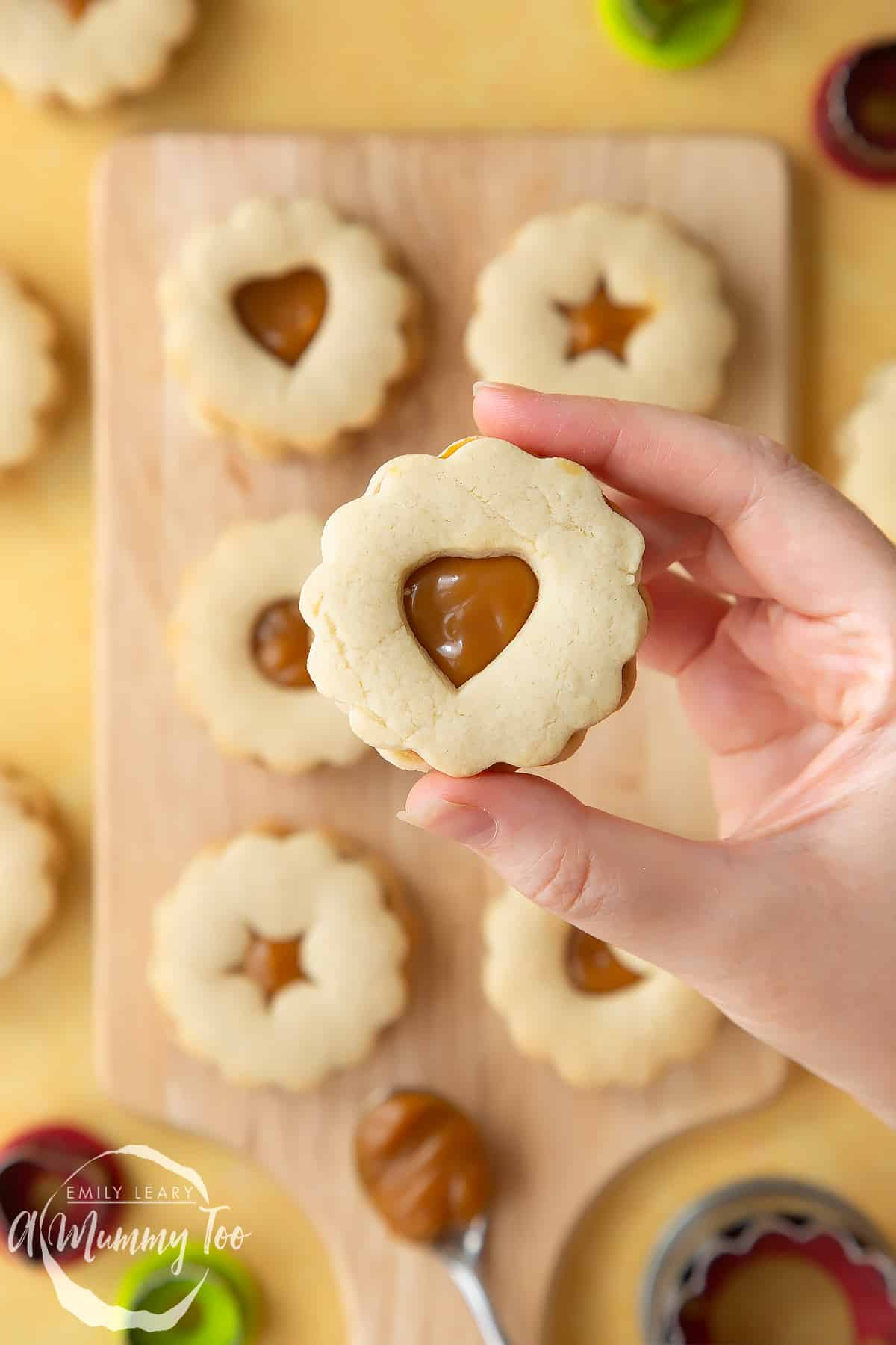 Hand holding a caramel sandwich cookies with additional caramel sandwich cookies in the background.