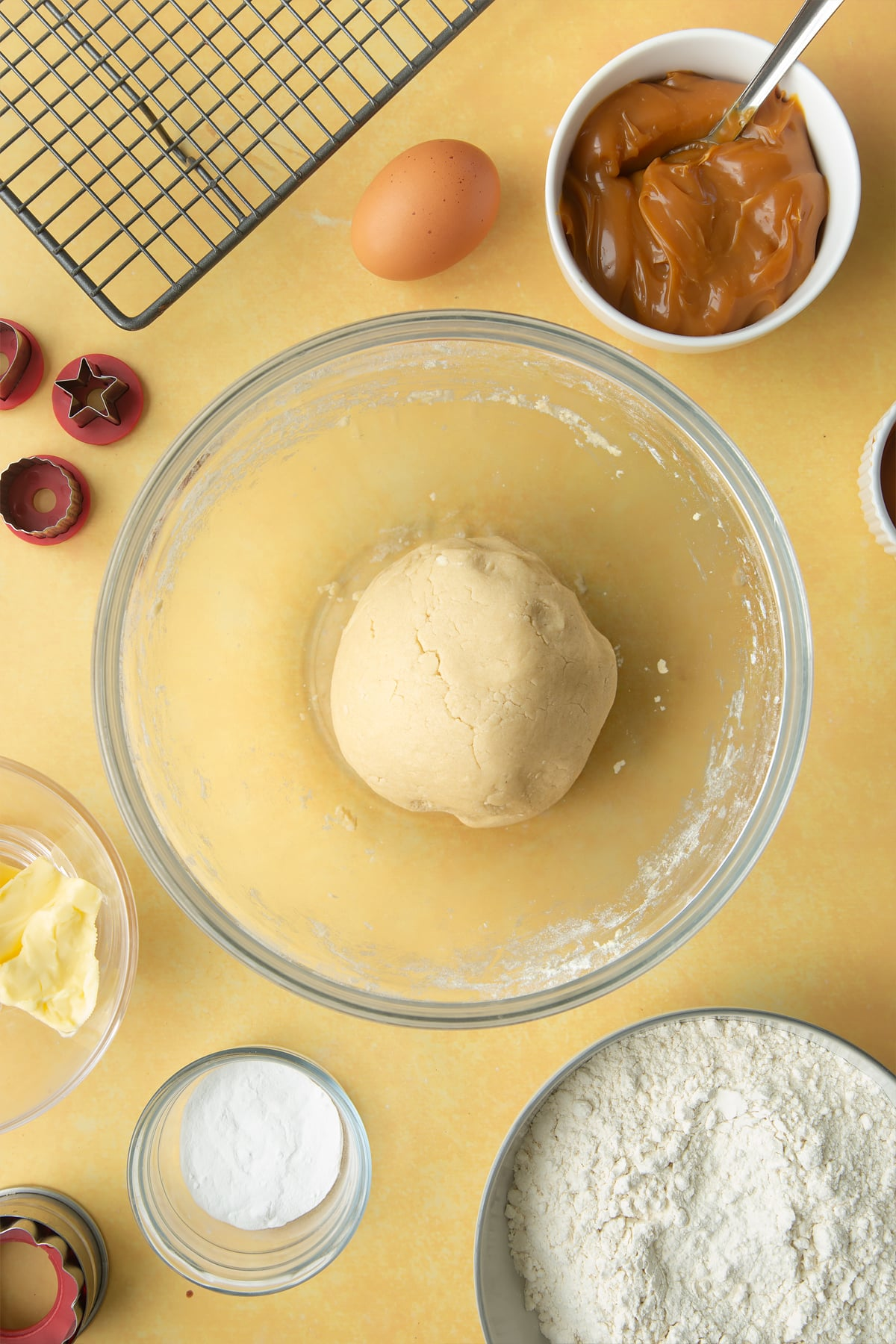 Overhead shot of a ball of dough in a large clear bowl