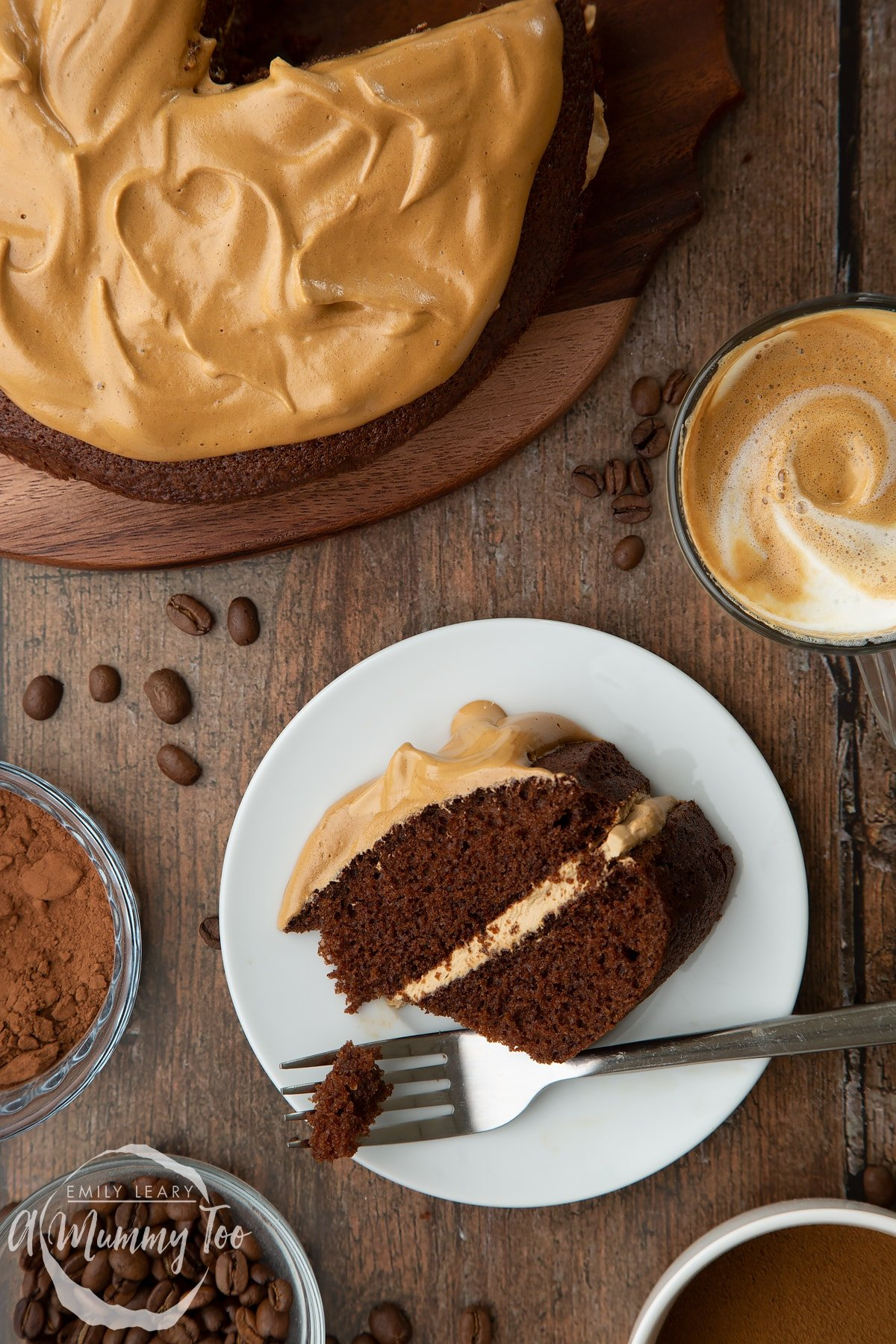 A slice of dalgona coffee cake on a white plate. A fork has taken a piece. A cup of dalgona coffee, cocoa and coffee beans are shown to the sides.