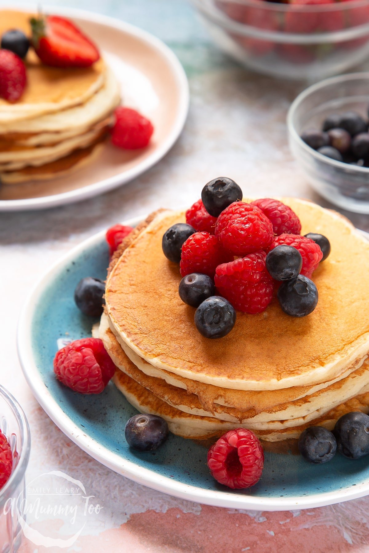 Stack of skyr pancakes on a blue plate. The pancakes are topped with blueberries and raspberries. Another stack of pancakes is shown on a pink plate in the background.