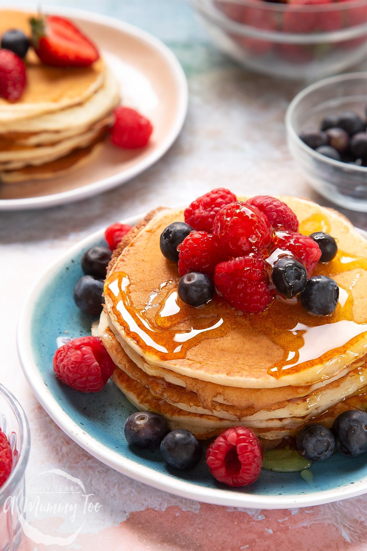 Skyr pancakes piled on a blue plate with blueberries, raspberries and honey on top.