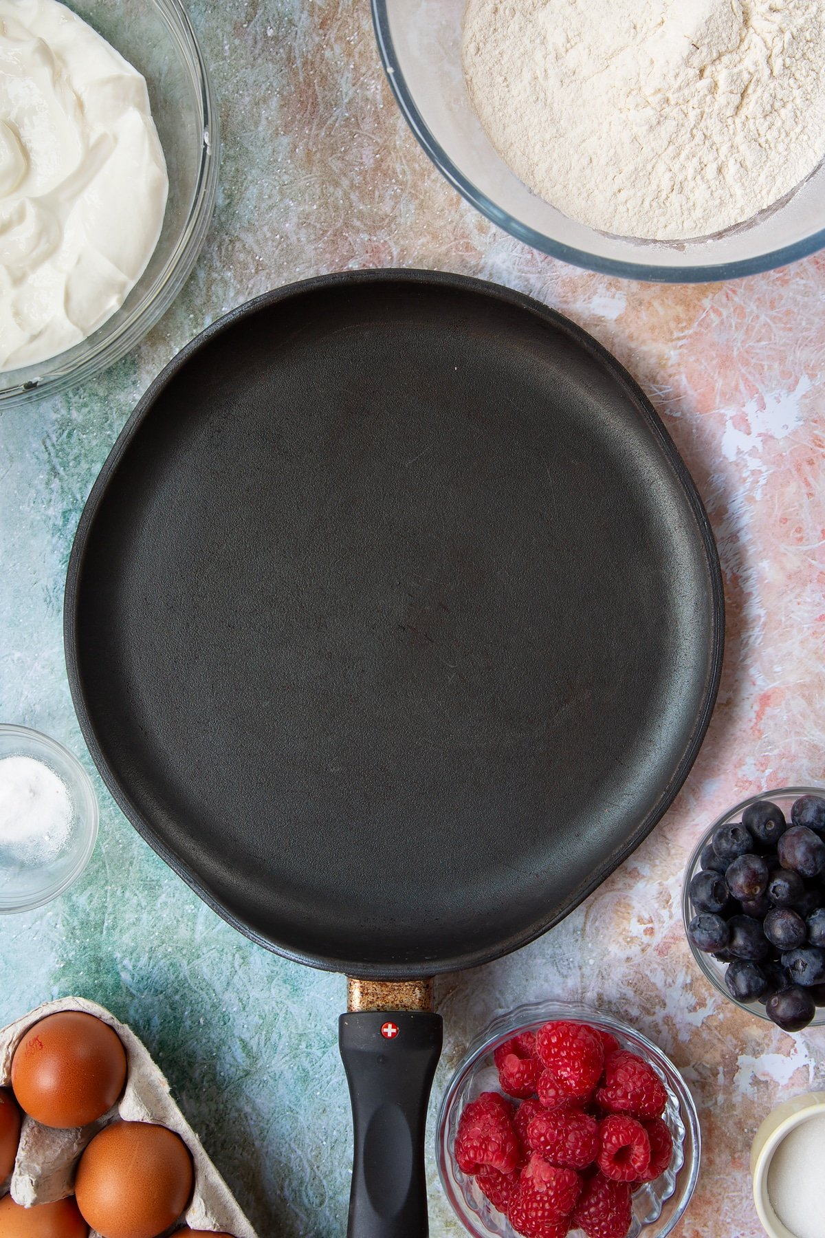 A hot frying pan. Berries and ingredients to make skyr pancakes surround the pan.