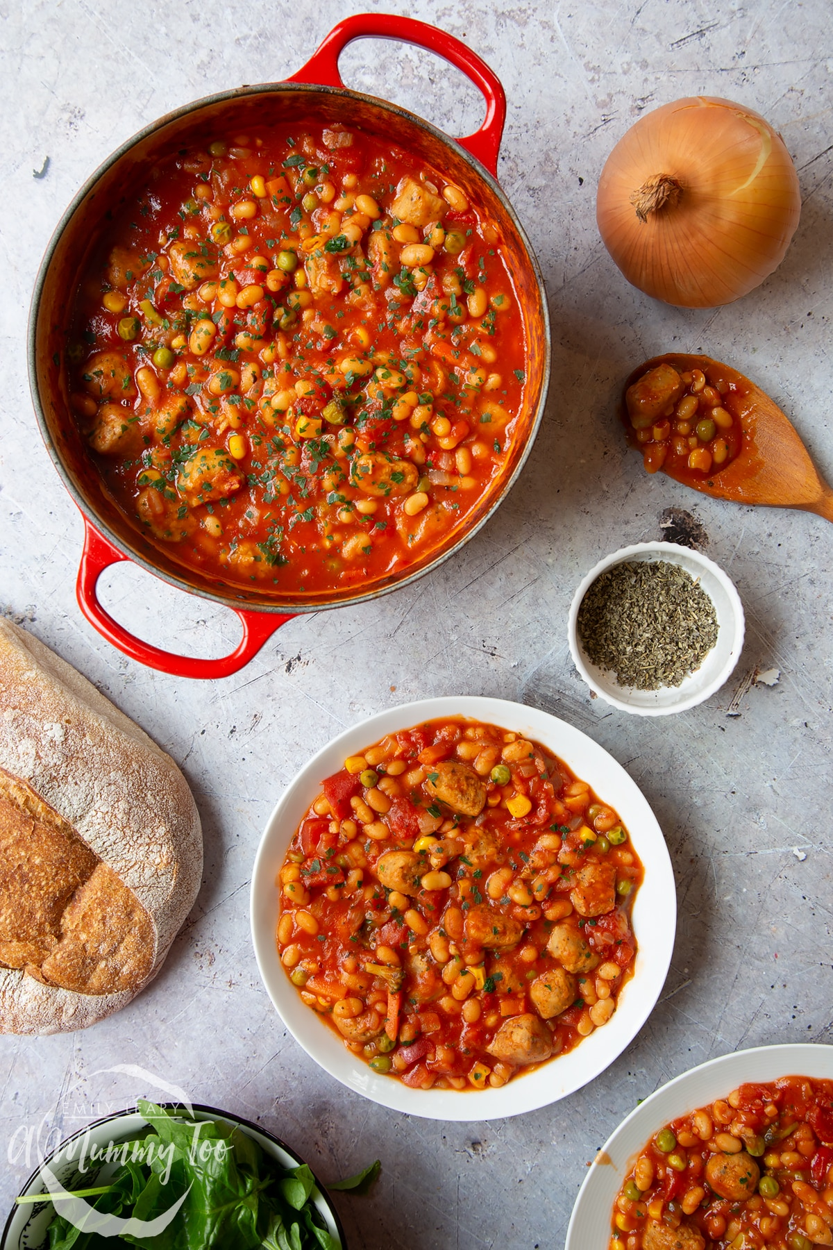 Veggie sausage and bean casserole served into a shallow white bowl. A large pot of casserole is also shown alongside a large loaf of crusty bread.