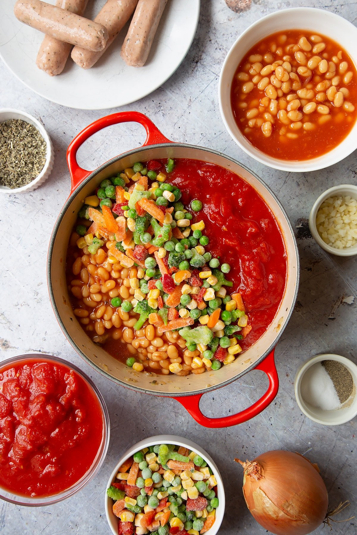 Fried onions and chopped vegetarian sausages in a large pot with beans, chopped tomatoes and frozen chopped vegetables on top. Ingredients to make veggie sausage and bean casserole surround the pot.