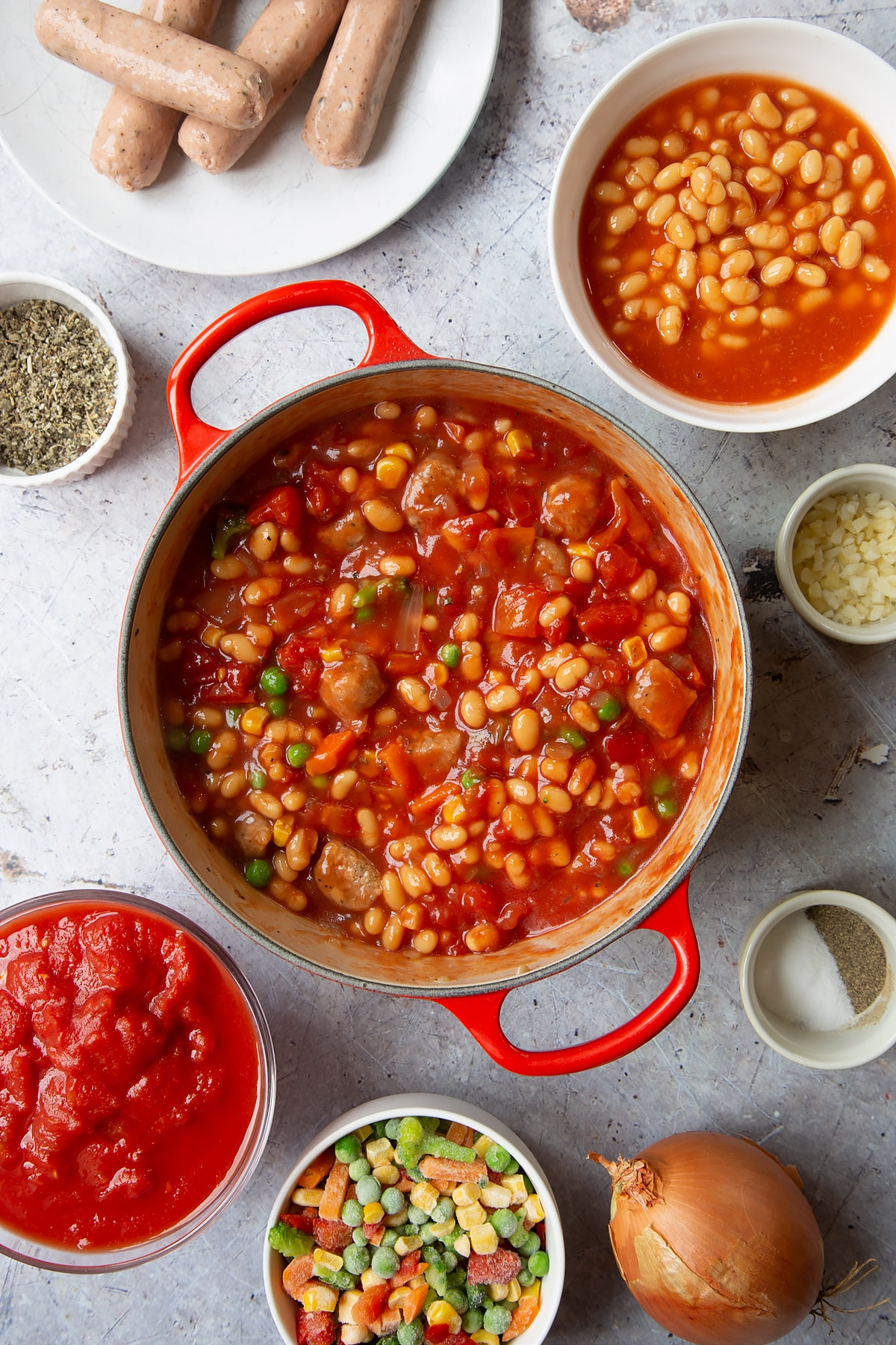 Fried onions, chopped vegetarian sausages, beans, chopped tomatoes and frozen chopped vegetables mixed together in a large pot. Ingredients to make veggie sausage and bean casserole surround the pot.