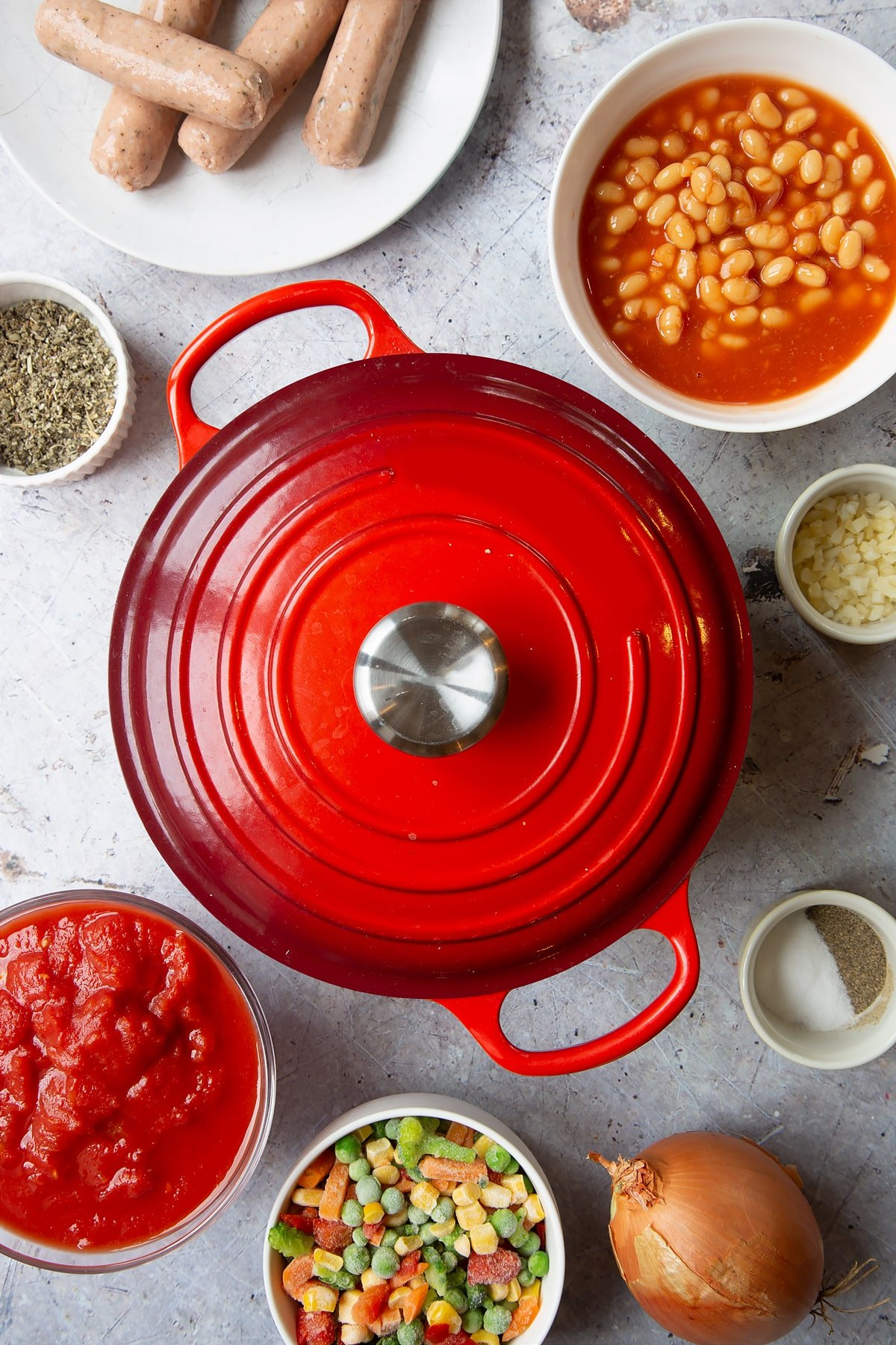 Large pot with red lid on. Ingredients to make veggie sausage and bean casserole surround the pot.
