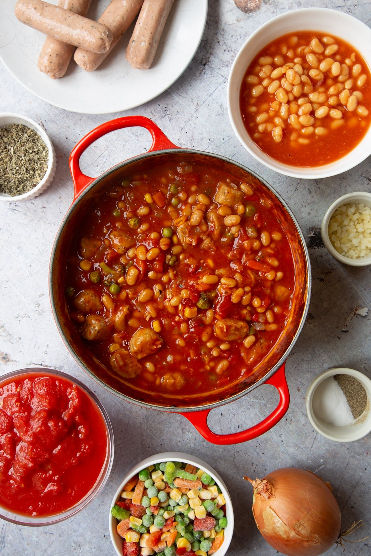 Vegetarian sausage and bean casserole in a large pot. Ingredients to make veggie sausage and bean casserole surround the pot.