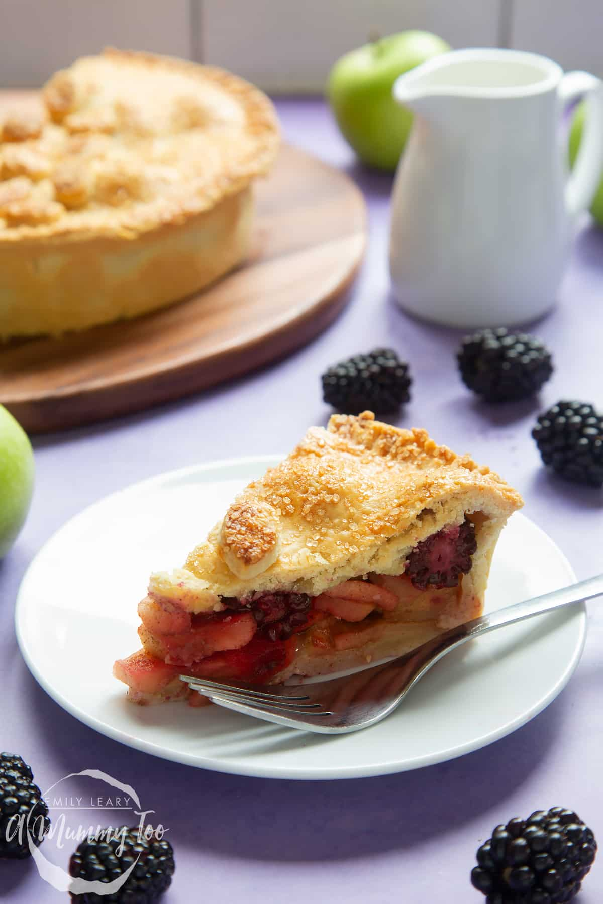 A slice of apple and blackberry pie on a white plate with a fork.