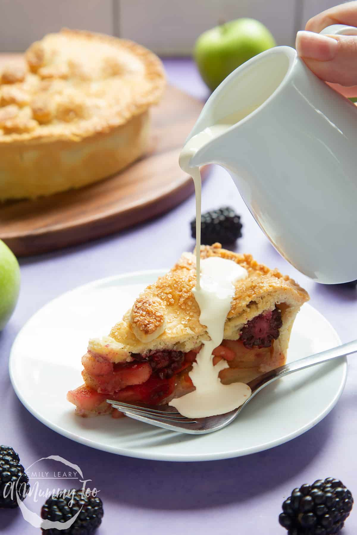 A slice of apple and blackberry pie on a white plate with a fork. A small white jug pours cream onto the pie.