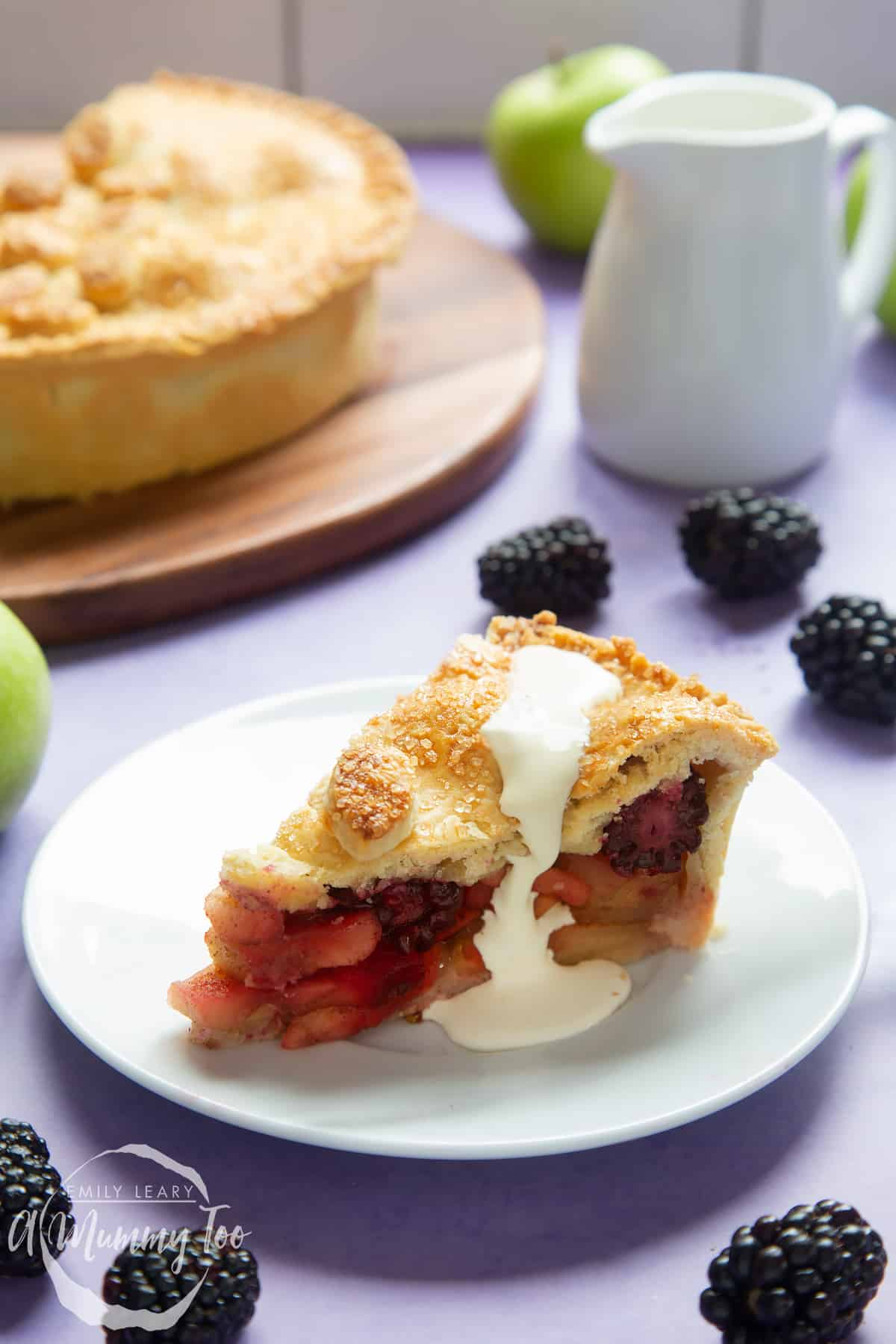 A slice of apple and blackberry pie on a white plate. Cream has been poured on top.