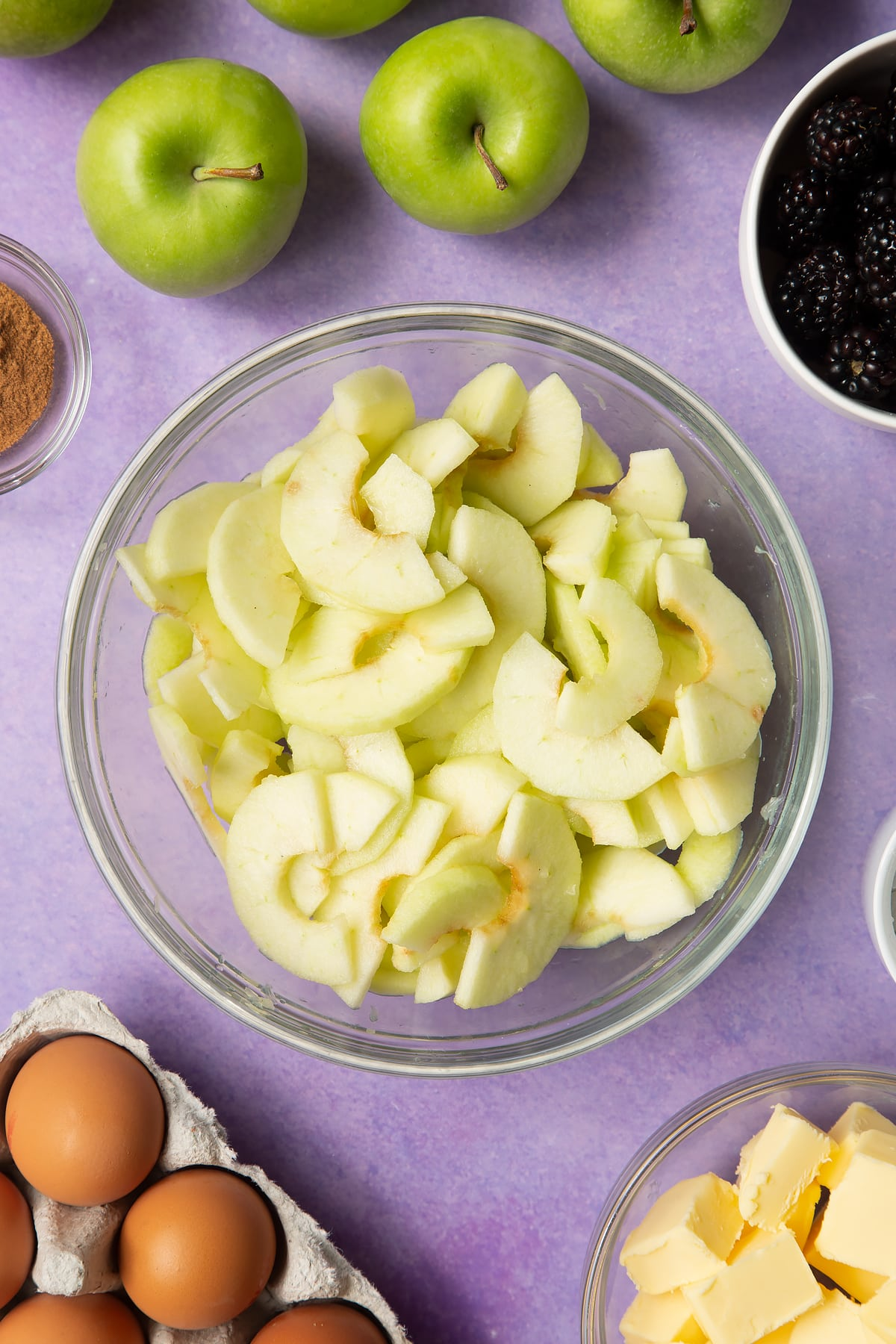 Apple slices in a glass mixing bowl. Ingredients to make apple and blackberry pie surround the bowl.