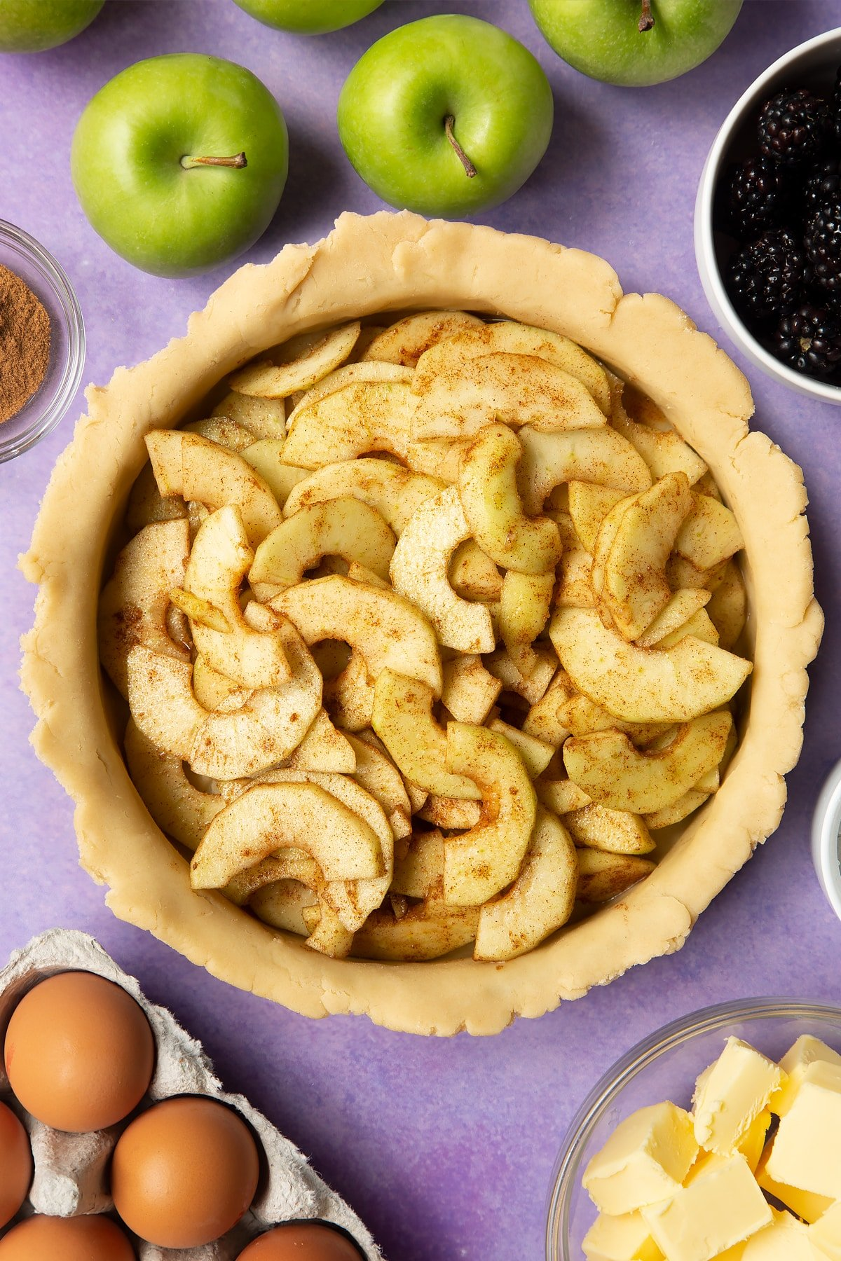 A pie tin lined with pastry and filled with cinnamon apple slices. Ingredients to make apple and blackberry pie surround the tin.