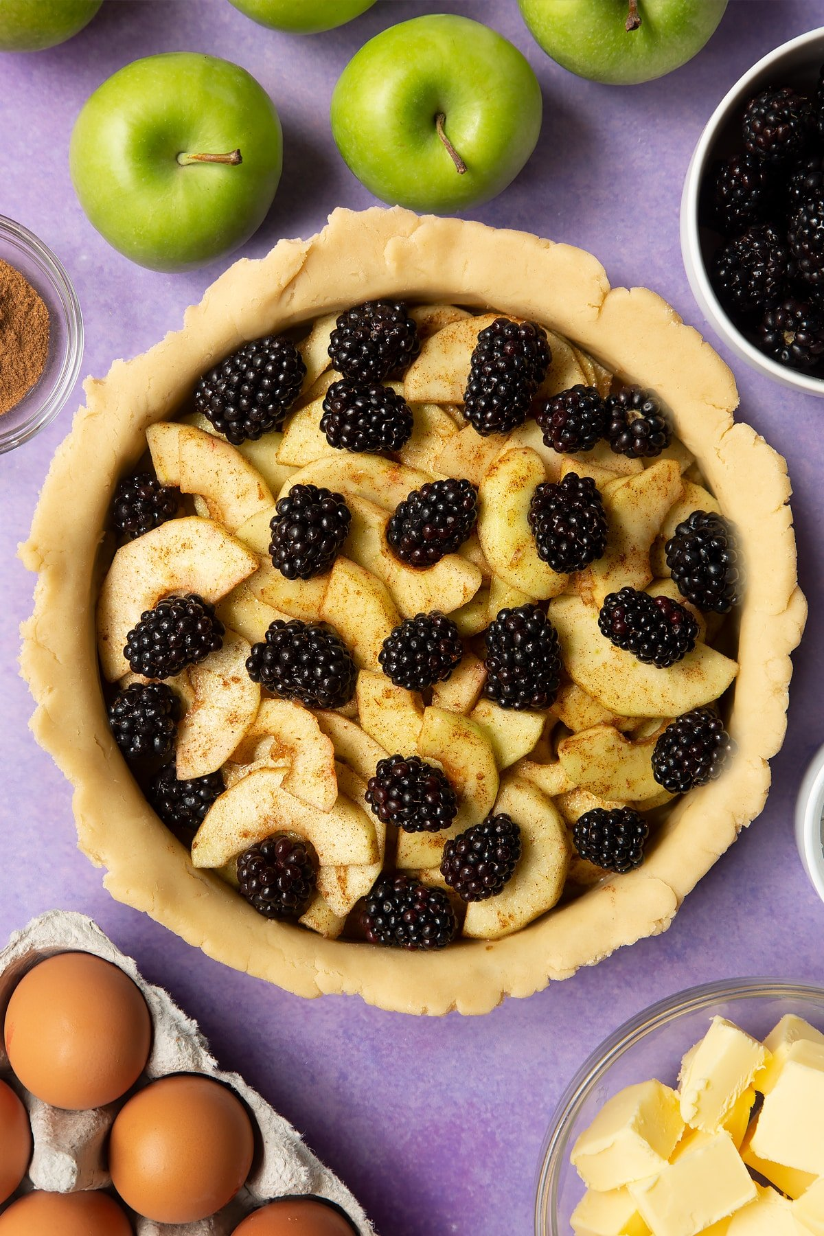A pie tin lined with pastry and filled with apple slices and blackberries. Ingredients to make apple and blackberry pie surround the tin.
