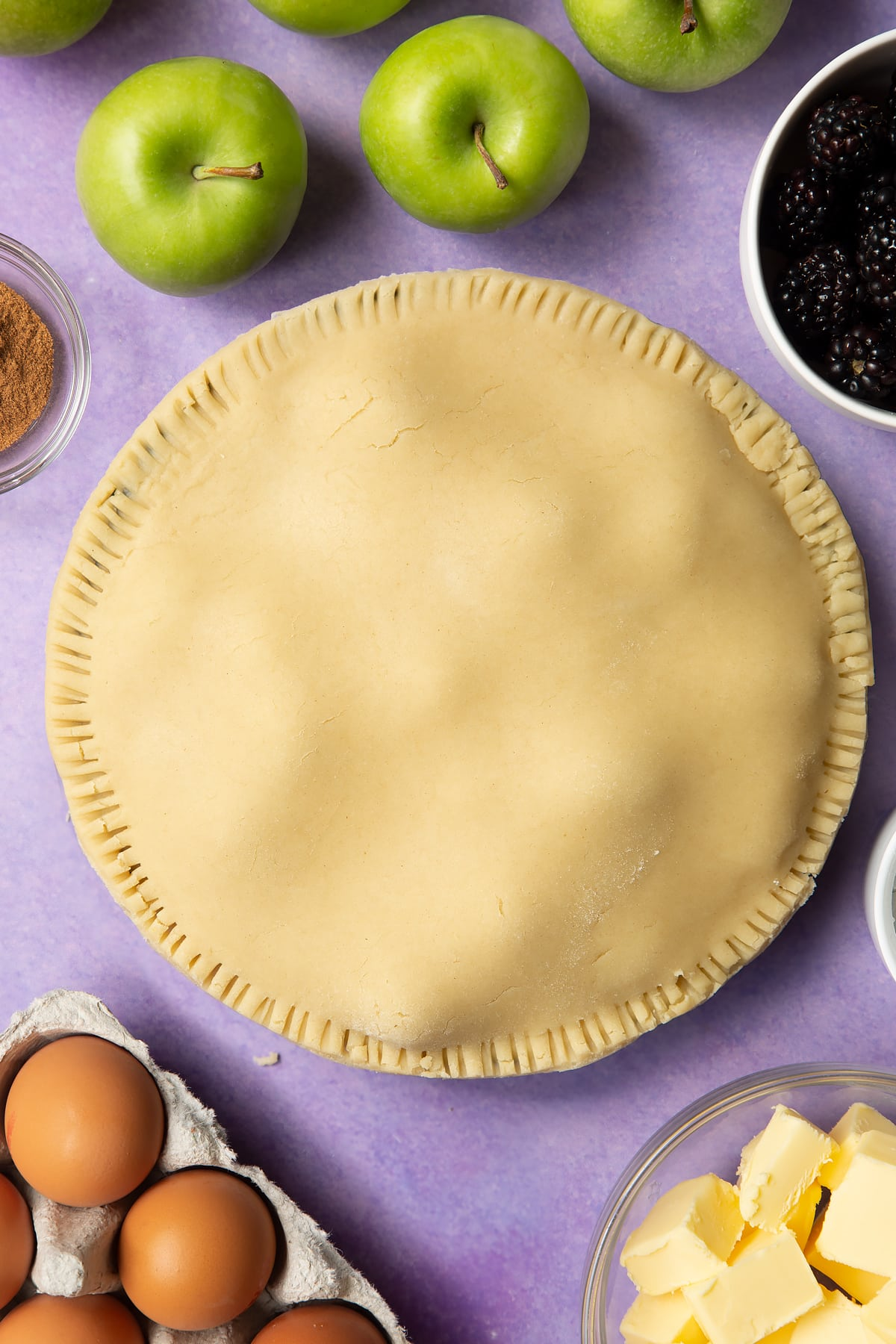 A raw apple and blackberry pie in a tin.
