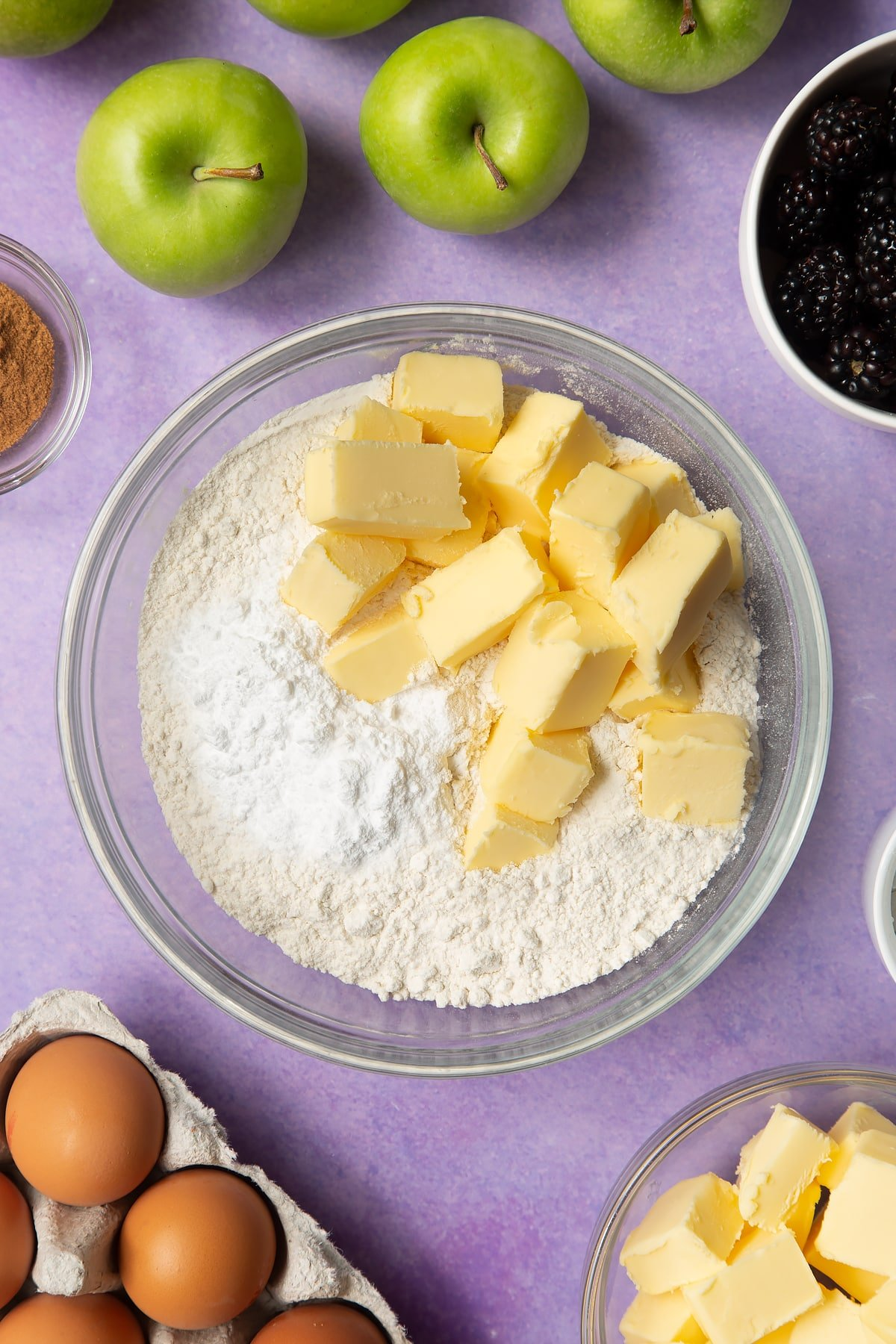 Flour, icing sugar and butter in a glass mixing bowl. Ingredients to make apple and blackberry pie surround the bowl.