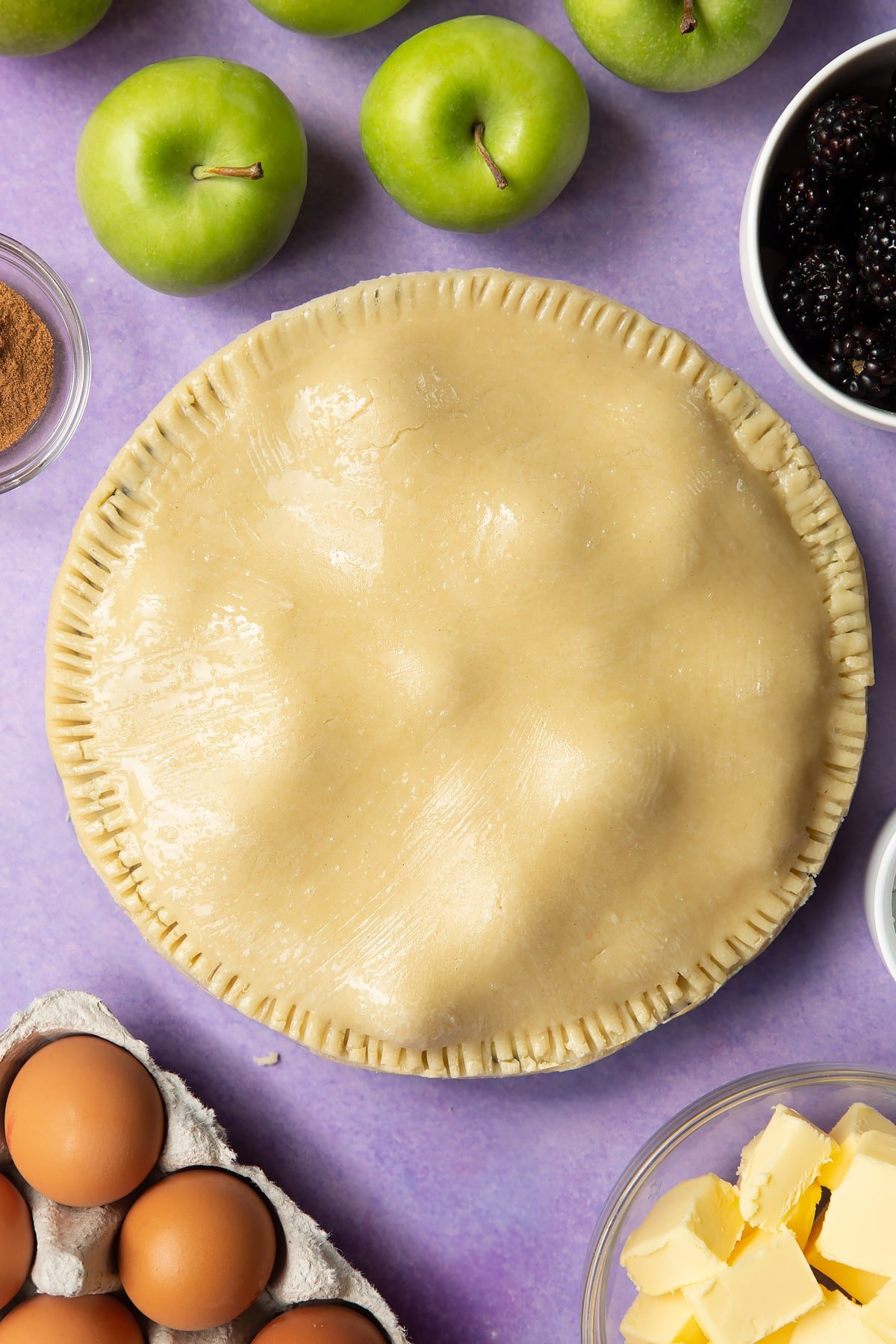 A raw apple and blackberry pie in a tin. The top has been brushed with egg white.