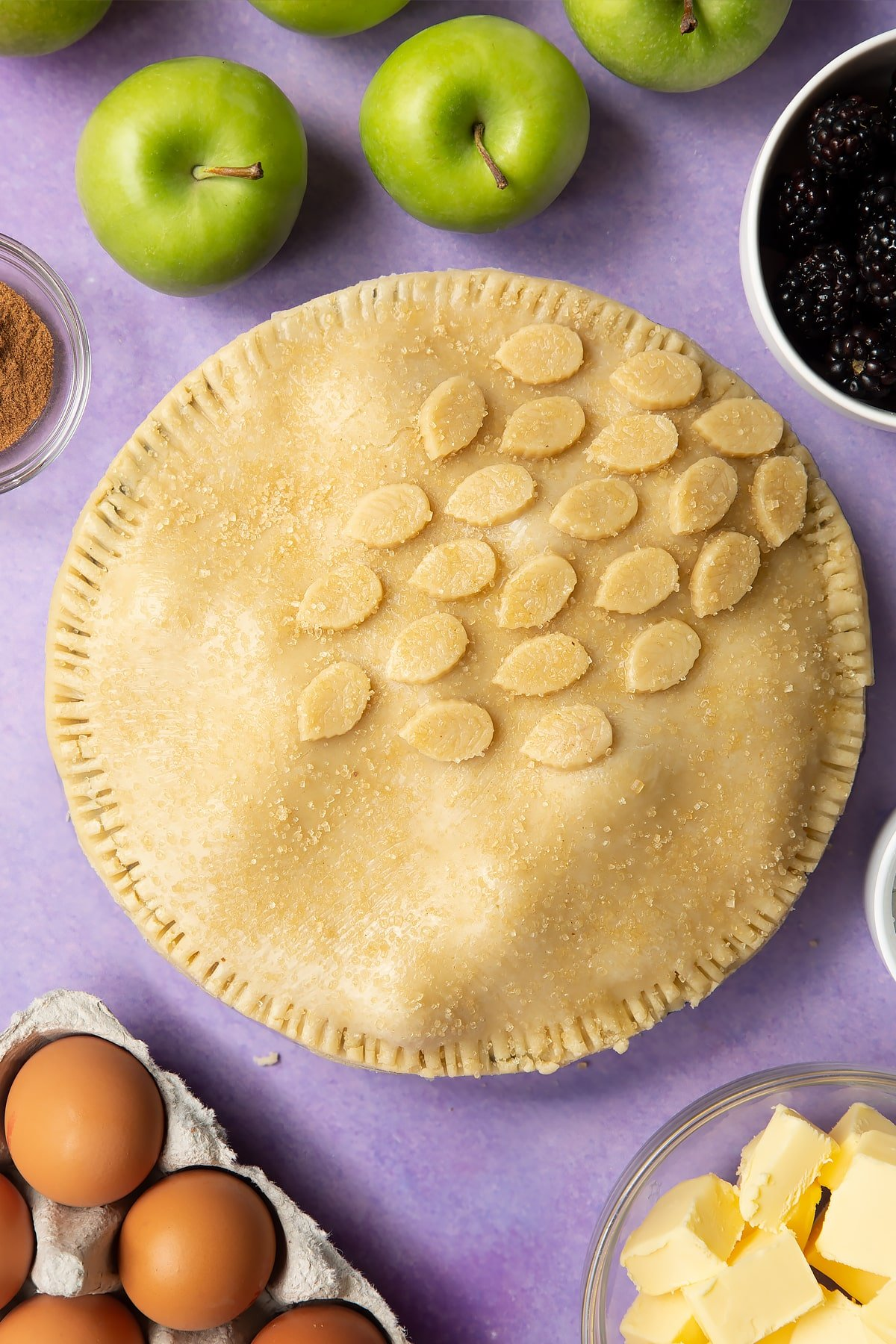 A raw apple and blackberry pie in a tin. The top has been brushed with egg white, decorated with pastry leaves and sprinkled with sugar.